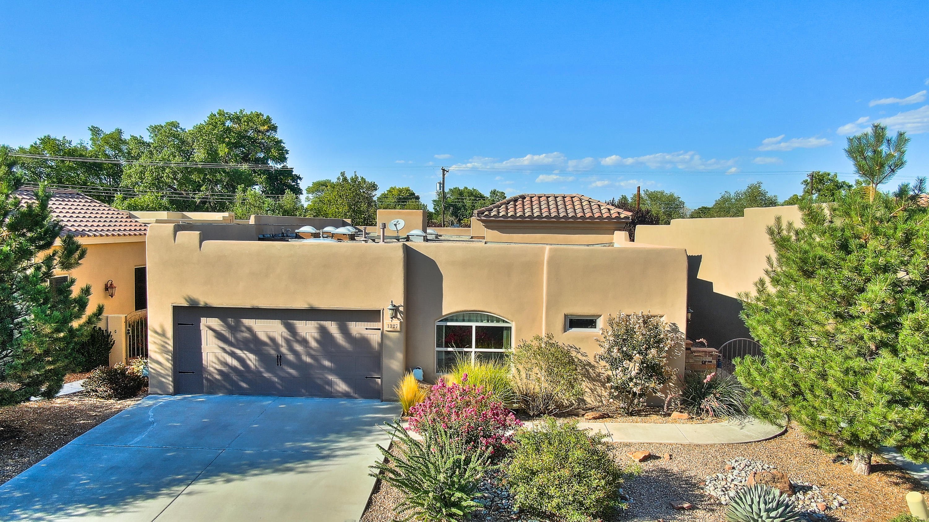 The perfect celebration of contemporary Southwestern design nestled in the heart of Albuquerque's North Valley! Gracious sun filled entry leads to expansive, open, great room with raised ceilings, and wood burning classic Kiva fireplace . Open kitchen with snack bar, custom cabinets, granite counters and upgraded appliances. Separate service room with wet sink.Informal dining space. Separated Owners quarters has a private bath with dual vanities, jetted tub,separate shower and walk-in closet! 2 additional bedrooms share a Jack and Jill full bath! Loads of skylights flood this home with natural light!Cozy rear patio out back! Ceiling fans, glass block accents and more! 2 car finished garage. Gated entry!Conveniently located for all of your needs! This Pueblo charmer won't wait! See it today