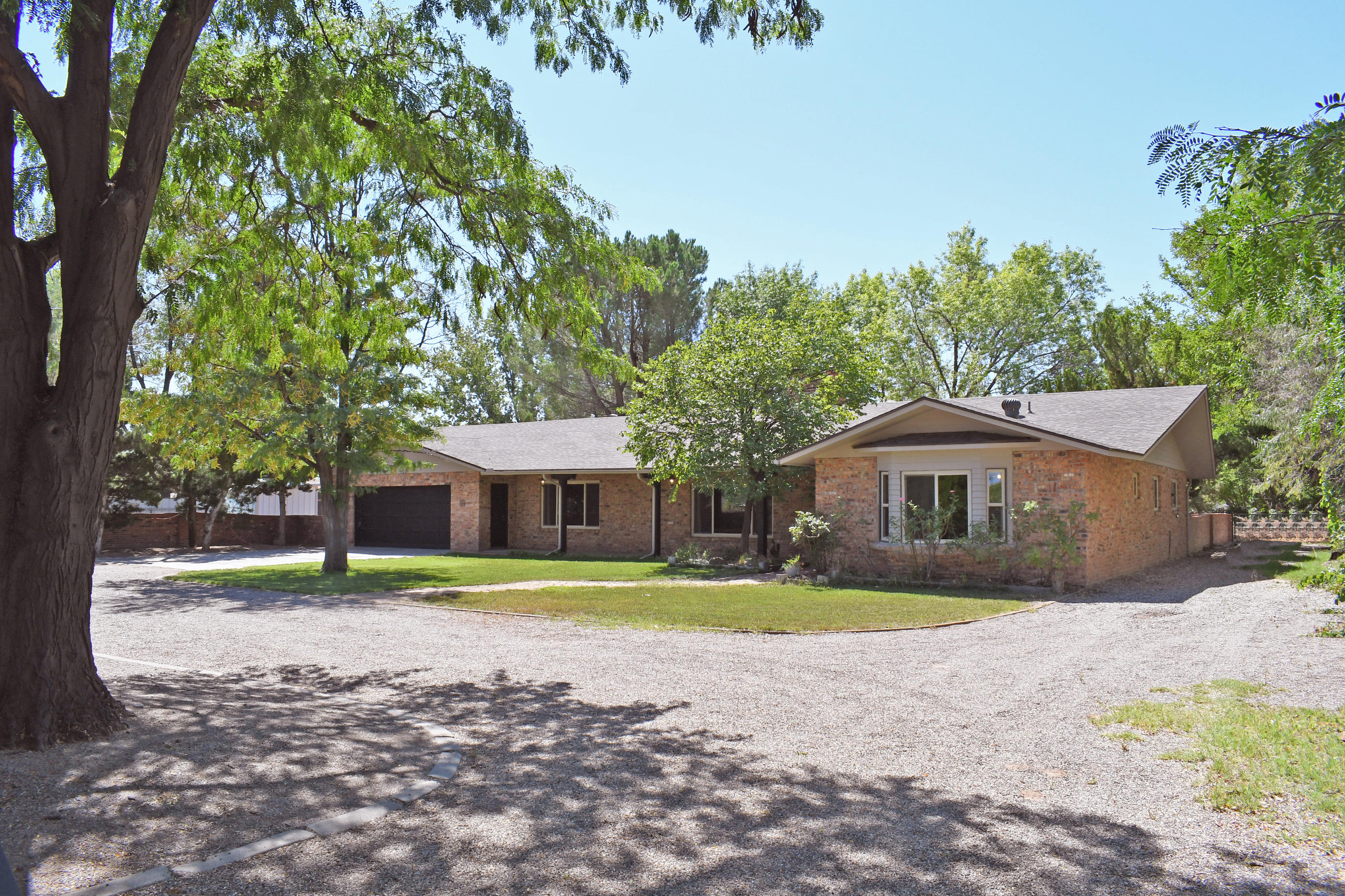 Welcome to the Drunken Brick Ranch Home. Drunken Brick is a waving brick pattern. Very beautiful effect. Drive in into the gated half moon driveway. Lovely front yard, freshly painted exterior facia and posts. Double masters, large living room with an expanse of great open formal dining room. 2 Wood burning fireplaces. Lovely kitchen with beautiful warm cabinets/ Stainless island. Family room open to the sunroom has a number uses ,office, plants, playroom, anything you can imagine. All the landscaping is on a irrigation Well. The house is on city water and sewer. The backyard is separated by a brick wall. Play yard and possible garden area. Room to build a barn  or work shop.This property let's you imagine a future in a peaceful place.  New Roof 8/2019