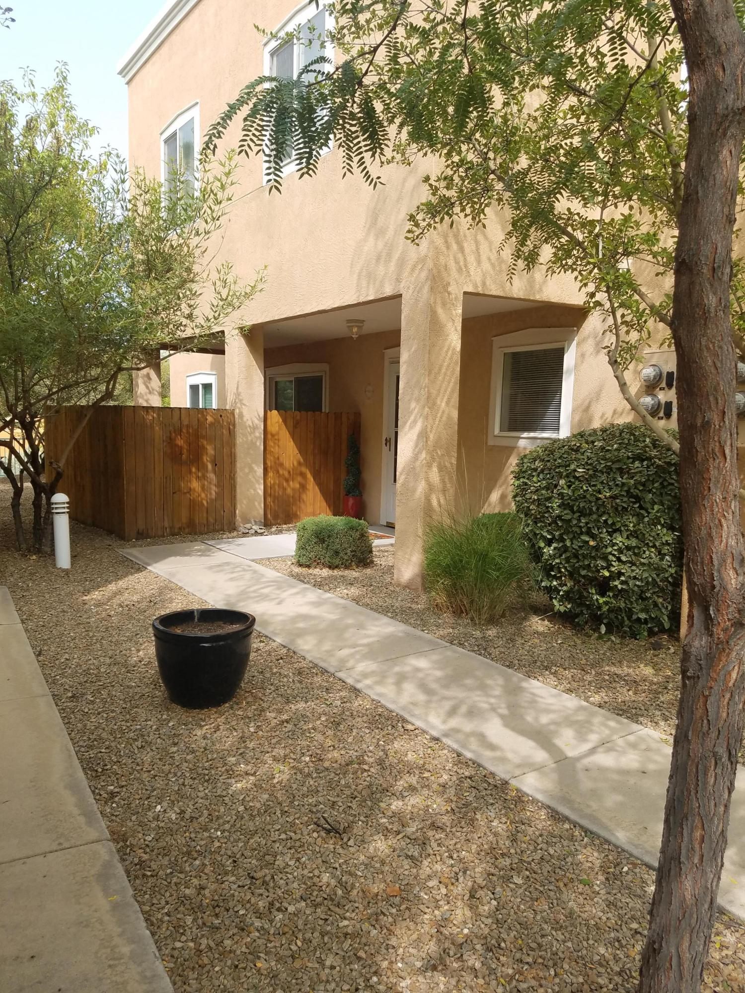 Great 3 bedroom, 3 bath Condo in highly desired NE Heights gated community.  New paint throughout, new swamp cooler, wood laminate flooring downstairs. Bedrooms on upper level with amazing views of the Sandias. Living room has gas fireplace and right off of living room is covered patio. Laundry room and half bath right off of dining room. 1 car garage with opener. Walking/Bike path right out your door and huge park nearby.  Great views ~ Great Location!