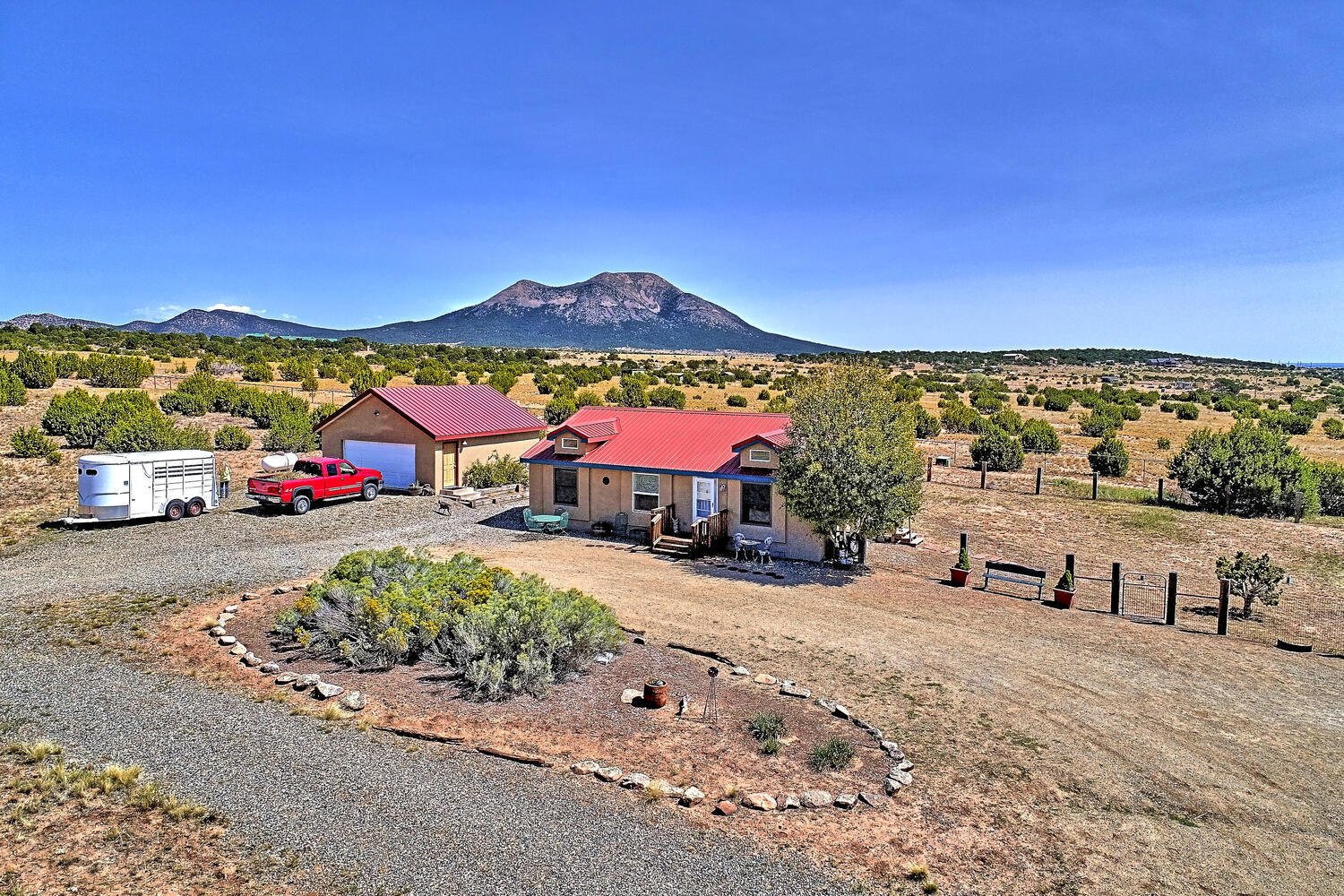 Imagine gorgeous Mountain views, beautiful sunrises and the full moon over South Mountain as you watch your horses or alpacas play on your own 10+acre ranch! Unique equestrian estate with a wonderful home, originally designed as a guest house. Live here while you build your dream home, or keep it simple and live forever in the UPGRADED 1080 SqFt home! This popular open and bright floor plan is Upgraded w/ Stucco finish/Metal roof/Detached 2 car garage/Double insulation for energy efficiency! Wonderful sunny kitchen boasts knotty alder cabinetry! Gas range/breakfast bar/eat in area/French doors! WOW!  70K + in QUALITY HORSE facilities! Pipe rail horse fencing/cross fencing/gates! 36x48 Castlebrook Barn elec+water! Usable 10 acres of Meadows and trees! Your own Ranch close to ABQ & Santa f