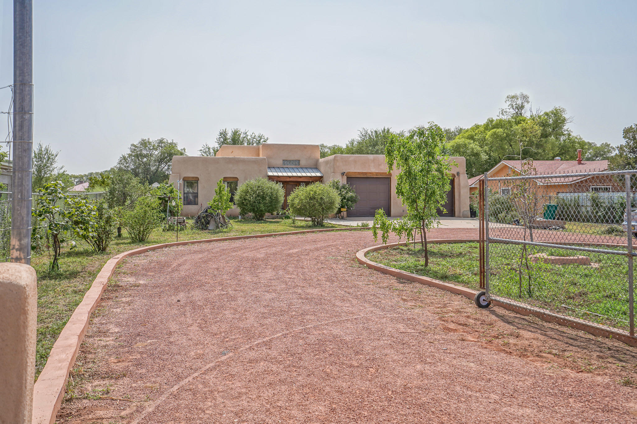 Enjoy the peaceful, green landscape of the South Valley, just minutes from the CNM Campus and a short drive to the Rio Grande.  Beautiful Tall ceilings with vigas, loads of natural light, new laminate floors in the main living space, new carpet and paint all on .7 acres of usable land.  Beautiful circular driveway and tons of options to landscape your private oasis on this large lot with a country feel.  Relax in your private master suite with a large walk in closet and full master bathroom with jetted tub, separate shower, double sinks and more natural light!  Enclosed patio offers additional living space for parties and relaxing.  Large garden areas where you can grow your own vegetables!  The garage features a double long space with a drive through to the back. RV Parking.