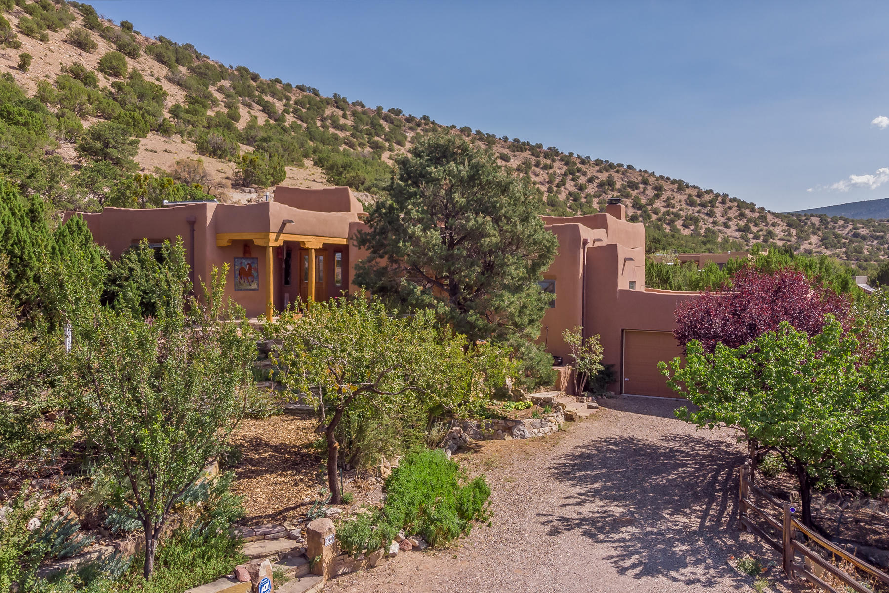 Enchanting Santa Fe style home nestled on 8.5 acres with adjacent 4.2 ac lot available to purchase.   Total SF includes: 2489sf MAIN w/4 bdrms,2full,1half bath, 2car gar; d 1458sf detached CASITA (2009)  w/kitchen, full bath, loft bedroom, LR, laundry/large STUDIO (approx. 650sf) w/half bath & storage. Custom designed and built as a peaceful oasis, surrounded by special spaces for quiet meditation and relaxation.Gardens, orchard, koi pond, trees,  native New Mexico wildflowers, amazing massive  rock walls and patios create n extensive retreat of your very own. Oversized wood windows bring beauty of the landscape & views to the rooms. The sky is amazing here, far from the city night glow the sky sparkles with a million galaxies. This property is on grid but generates is own electricity an