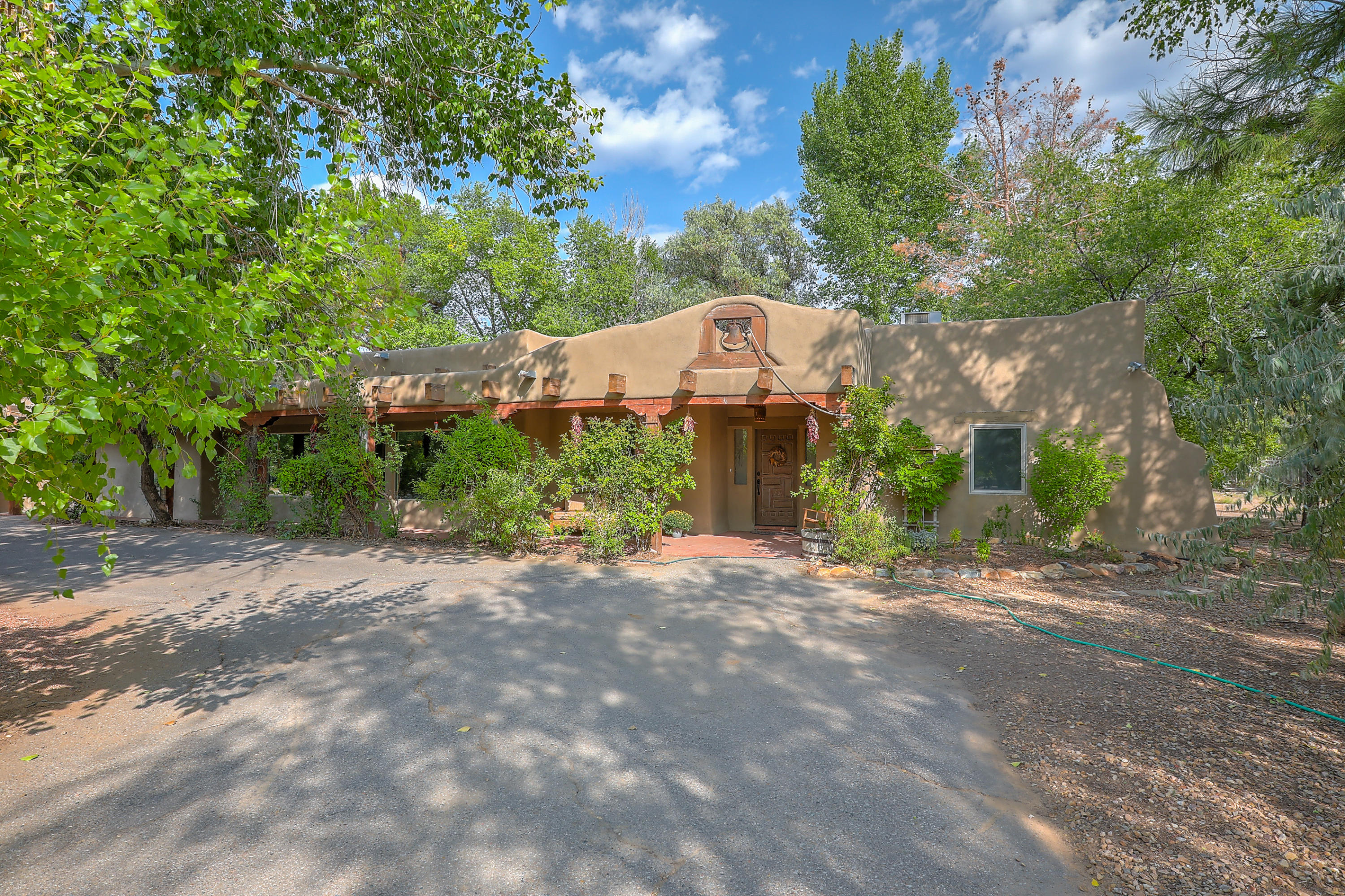 Corrales living just minutes from Albuquerque. This 2.85 acre property offers space for animals and room to roam. Remodeled in 2013 and offers upscale amenities including a chef's kitchen, open concept great room, lots of windows and a dramatic fireplace. Brick floors and wood beams offer the SW charm while the upscale amenities make life here easy. Enjoy the large master bathroom, separate walk in closet and outside patio access. The sitting room/study off the master is cozy with its own fireplace. The property includes a barn, exterior storage, piped fence horse pens and plenty of acreage for a dressage or jumping arena. This will be someone's equestrian dream. The neighborhood boasts big lots, flat land with green grass and trees, plus just minutes to town for an easy, quick commute.