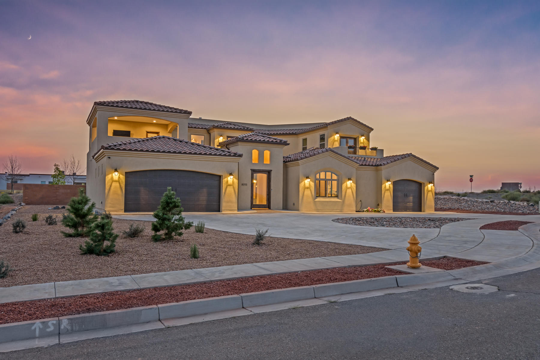 Beautiful Custom home in the desired Petroglyph Estates subdivision. Amazing views from 3 available balconies. 8' Solid Alder wood doors, Granite counters, Cantera Columns, Faux finish paint in entry/kitchen tower. $20k of custom window covers.  $10K whole house water filtration system. 2 tankless water heater-this home is engineered high efficiency with Refrigerated air. MIL suite with separate garage and separate entrance can double as a work from home office.  Private court yard with fountain and flower beds make this the perfect get-away. Jack and Jill bathroom in upper floor-master/laundry room on main. Bronze level green built-it.  Vivant alarm system, Arlo cameras and Sonos surround sound system.  Balloon fiesta and views from 3 directions.  You need to see this beautiful home.