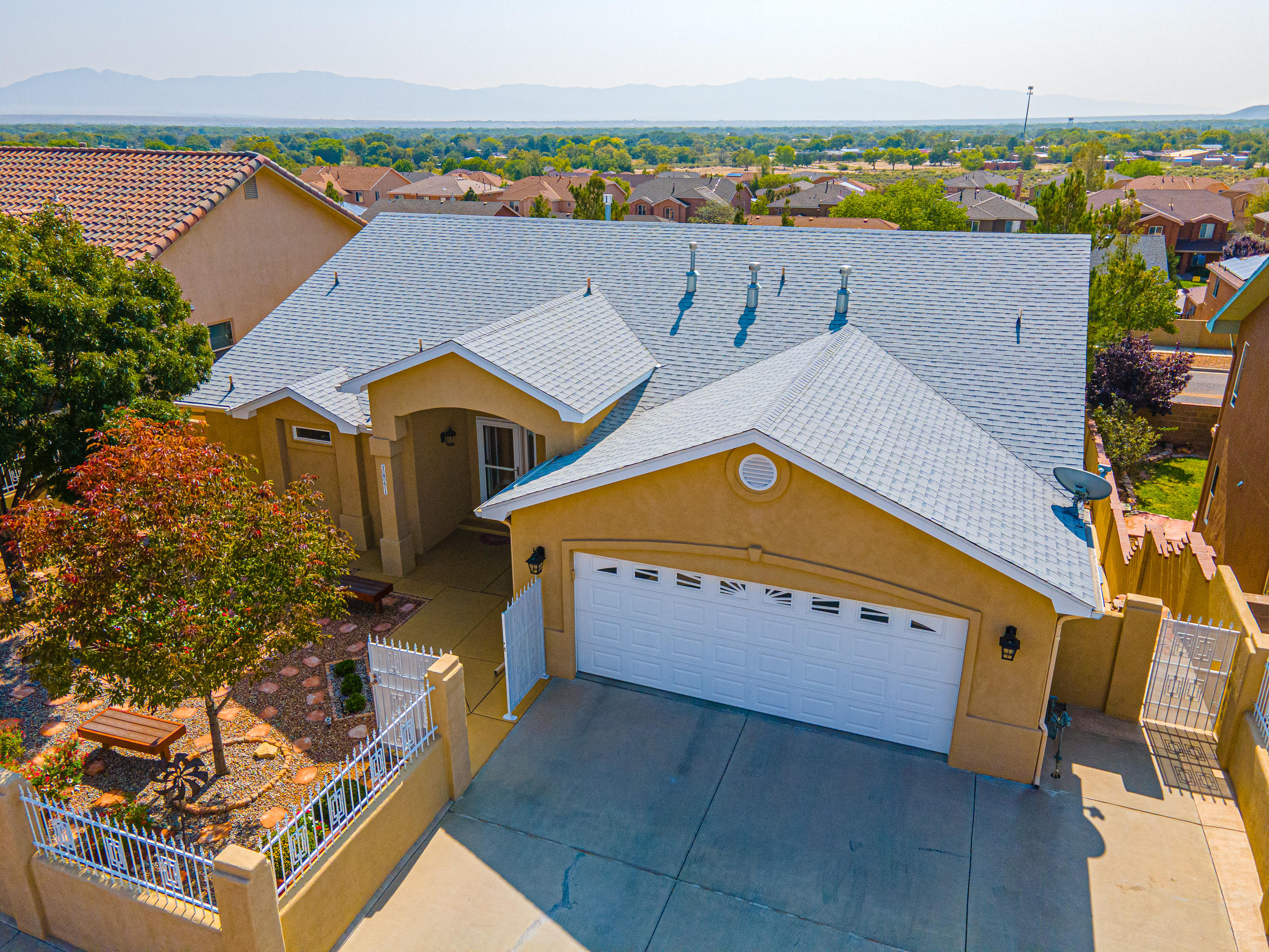 Wow! Beautiful custom home with fabulous mountain & city views from deck, master bedroom, living room & dining room.  Front of home appears to be single story with main living area at street level with downstairs 2 bedrooms, full bath with game/recreation room. Lots of upgrades include granite, appliances, lights, maple & oak wood flooring, crown molding, faucets/fixtures, hugely expanded deck & covered patio area, rain gutters & sidewalks all around the home, rock stairway on west side.  Yards professionally landscaped & on auto drip. Front courtyard fenced & secured, landscaped with benches, trees & beautiful planters filled with blooming plants. Walled backyard is a relaxing oasis with benches, trees & planter boxes.  Custom tool shop with dormer, electricity & HD shelving & workbench.