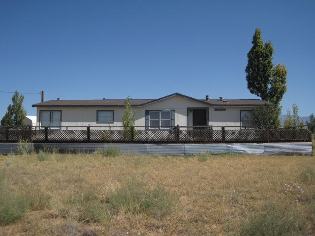 Come see this spacious manufactured home on 1.25 acres with meadow & mountain views! This home has 3 large bedrooms with walk in closets, laminate floors & 2 full baths. There is a metal 2 car garage with power for workshop area. The roof was replaced in 2019. The open living room has a wood burning fireplace, built in shelving, curio cabinet in dining room.  Double doors welcome you to a fully screened-in porch on the east side of home. The large kitchen has lots of storage and has a bright cozy breakfast nook. The house is towards the front of the lot and has ample space behind & 2 decks to enjoy the wide open views!  Call today to come see this home!