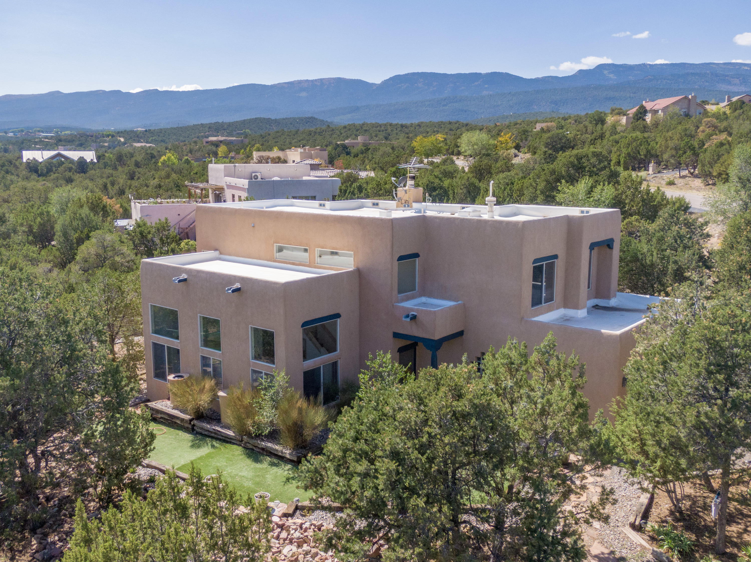 Welcome to this Bright, Beautiful, 1-Owner, Move-in Ready Mountain Home in Sandia Park! *Pool & Tennis Court Access for $250/yr!* Nestled on a Large 1.27 Acre Lot in the Desirable Paako Community, 44 Chaco Loop presents you with Breathtaking Mountain Views from Dawn to Dusk and a Forest of Lush, Green Trees! This Home offers 2 Light-Filled Living Areas and a Clean, Modern Kitchen with Stainless Appliances, Solid-Surface Counters, Island, Coffee Bar, and Breakfast Nook. Let a Custom, Wood Burning Fireplace w/ Log Lighter be your Family Room's Focal Point this Fall! Your Master Suite features a Private Balcony, Double Sinks, Garden Tub, Separate Shower, Walk-in Closet. Tile & Laminate Flooring Throughout. No carpet! Zoned, Radiant Heating. Tankless Water Heater provides Instant Hot Water.