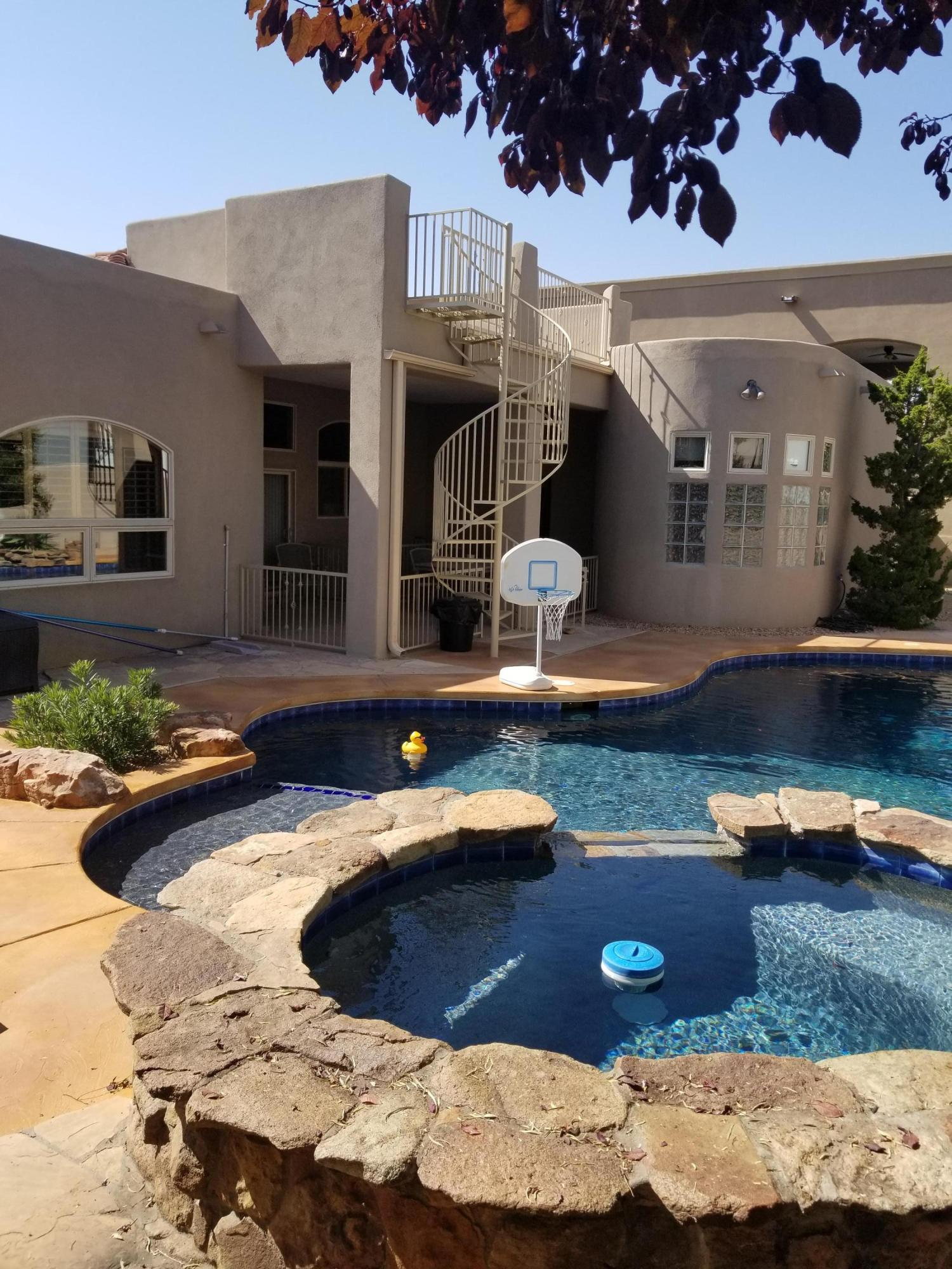 Gorgeous House w/ great Layout, Spacious, & backyard Pool/Spa Paradise! (With a Xeriscaped/Flagstone/Dog Run area). Gated Community! North ABQ Acres Area & Schools, w/ views of the Mountains!...Tile in All Bathrooms, Showers, Kithcen, Hallway, and Newer Tile in Dining Room that replaced carpet in 2016...Granite counters in Kitchen & Island...Fresh Paint throughout Sept. 2020...Newer Carpet main level 2016...New pool deck surface less than 1 yr...Newer Pool Heater & filter tank 2015...Newer Main Refrigerated A/C unit 2015...Newer Water Heater 2018...Newer Washer 2018...All Pool Equipment, Master Bath Vanity Mirror, & All Appliances convey, including second fridge/freezer in garage.