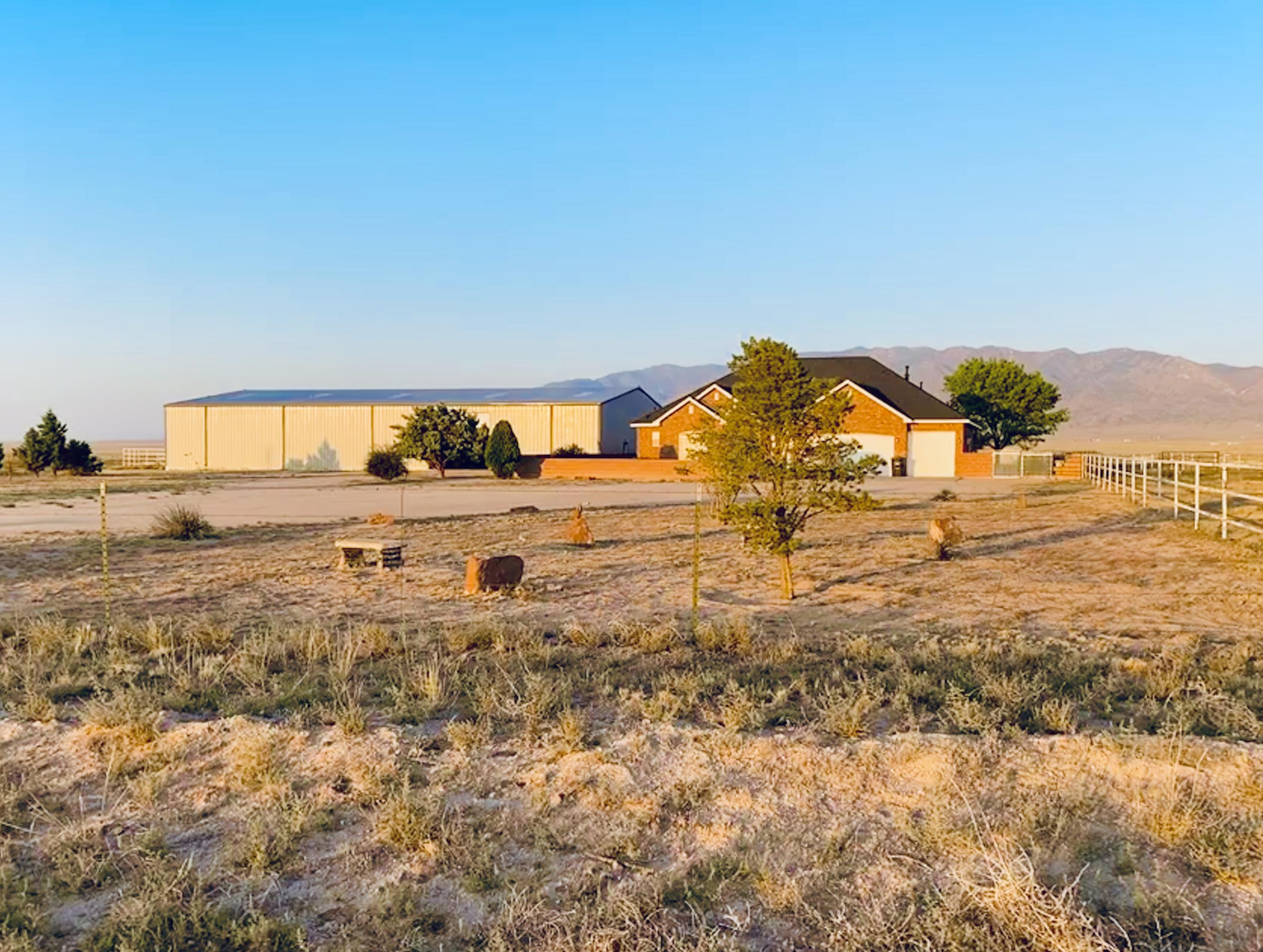 Beautiful Views of the Manzano Mountains, front row to New Mexico's Picturesque Sunrise and colorful Sunsets!  Horse Ranch, more than 23 acres with a 120 x 70 indoor riding/training arena. 4 stalls and tack room inside + 3 stalls outside. Pipe fencing, fully fenced on grazing land. An open foyer welcomes you to this four bedroom brick home with formal dining room, 2 living areas and a generous master suite. Enjoy bathroom accessibility from each bedroom. Gated electric entrance to property. Courtyard in front and back. Don't Miss out on this great opportunity to own this horse ranch property!!