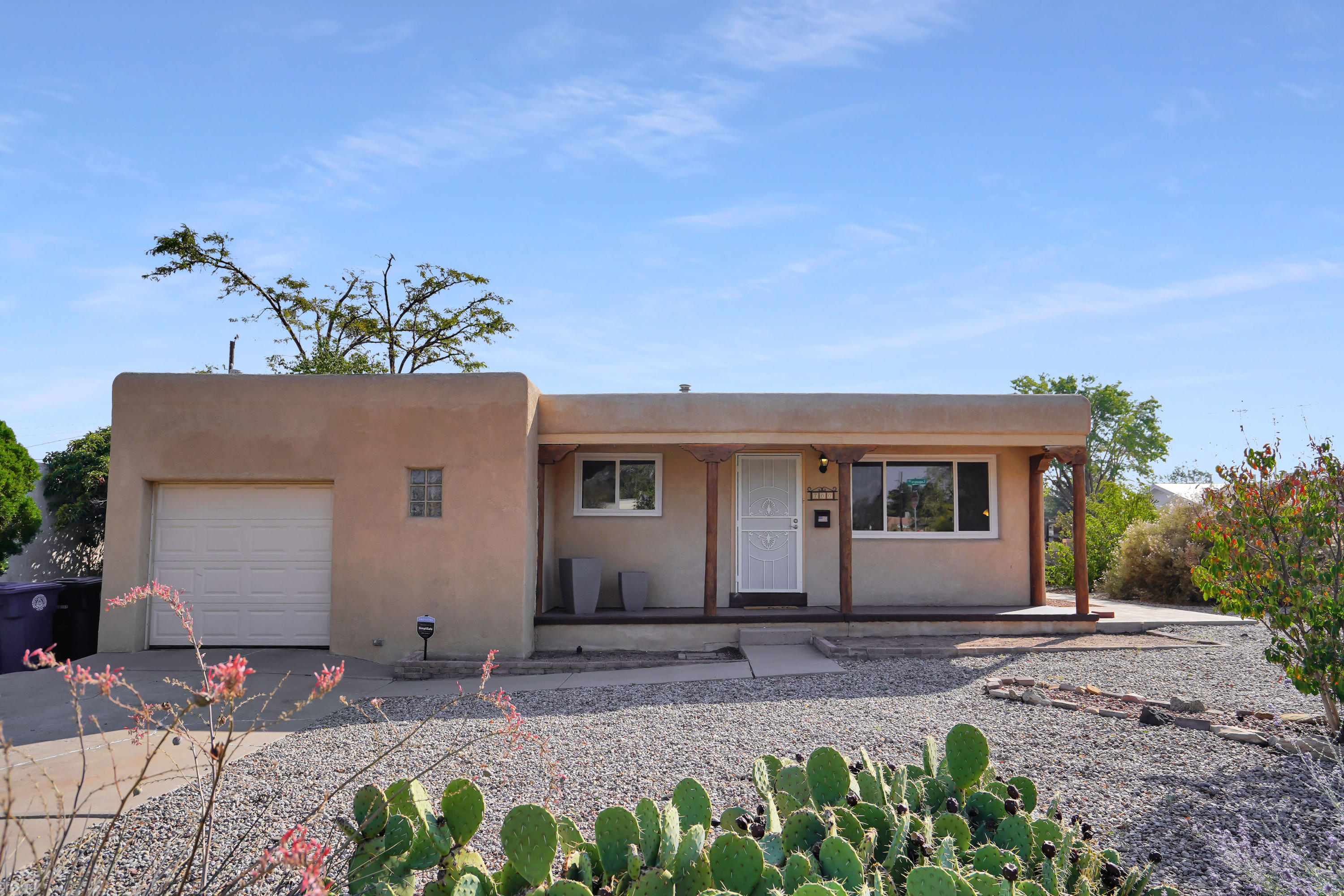 Welcome to this amazing Pueblo Style home situated on an oversized corner lot, featuring two spacious living areas, granite counter tops inside and out, and a garage with extra storage. Enter the home and you will see the refinished original hardwood floors throughout. To the left is the bar in kitchen, with impeccable granite and a chef's stove. The back room has enormous space for flexible usage. The three bedrooms continue the hardwood floors. Enjoy BBQing and entertaining in the backyard! Side yard has ample parking and the flowers are gorgeous in bloom! Close enough to high way access, Kirkland AFB, UNM, and malls. Windows under warranty! Come see it today!