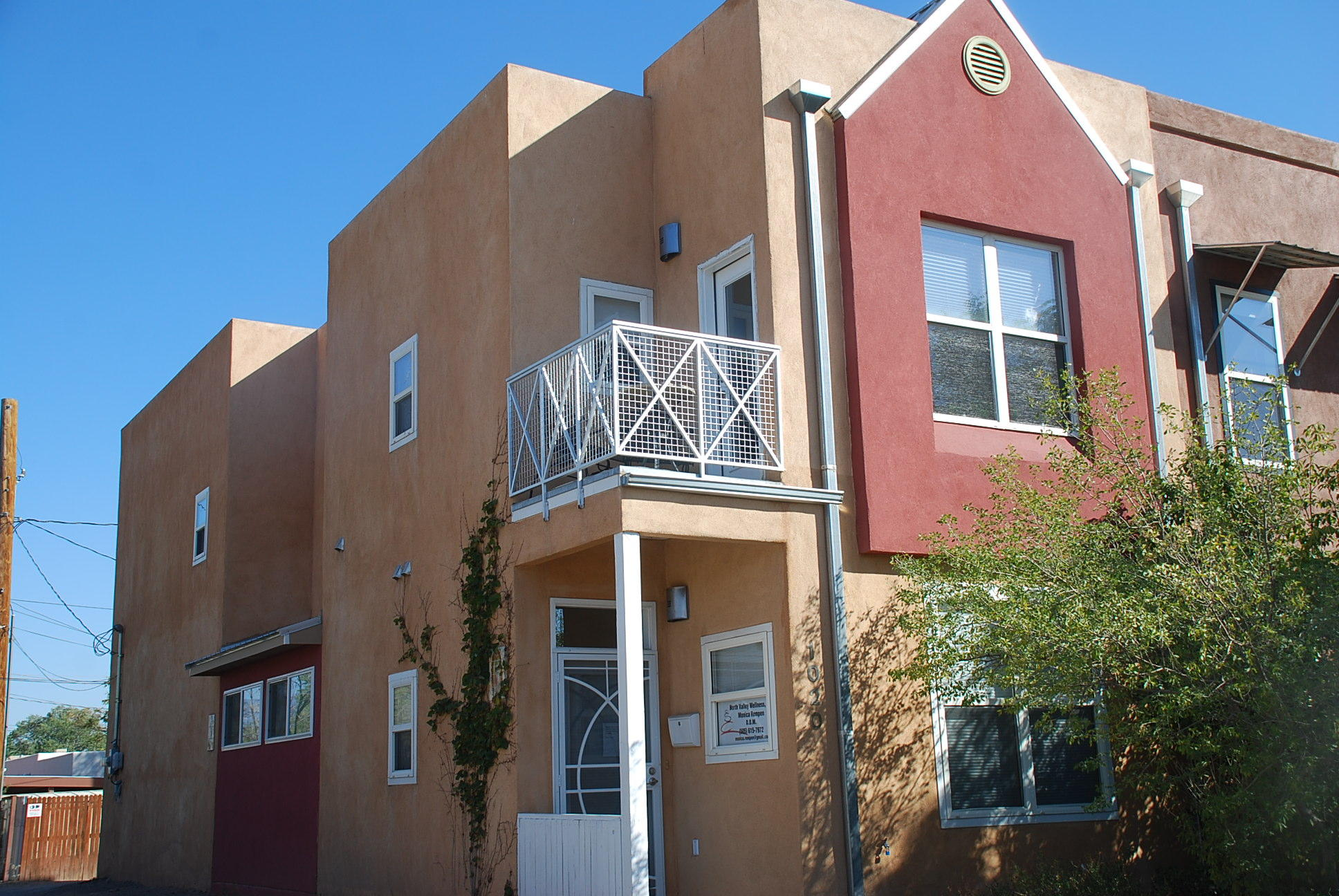 OFFERED AT $7,000 BELOW APPRAISAL! Modern, bright, and well kept townhome in a convenient location close to downtown, restaurants, breweries, cultural attractions. 3 bedrooms, 2 1/2 baths, 1-car garage plus carport. Upstairs wood floors, bedroom with mountain views and walk-in closet, kitchen has bar counter seating 3-4, 2 patios with city and mountain views. Ground floor stained concrete floors, office, 2 bedrooms. NO HOA. Zoned MX-L. Perfect home office,  retail, clinic, legal.