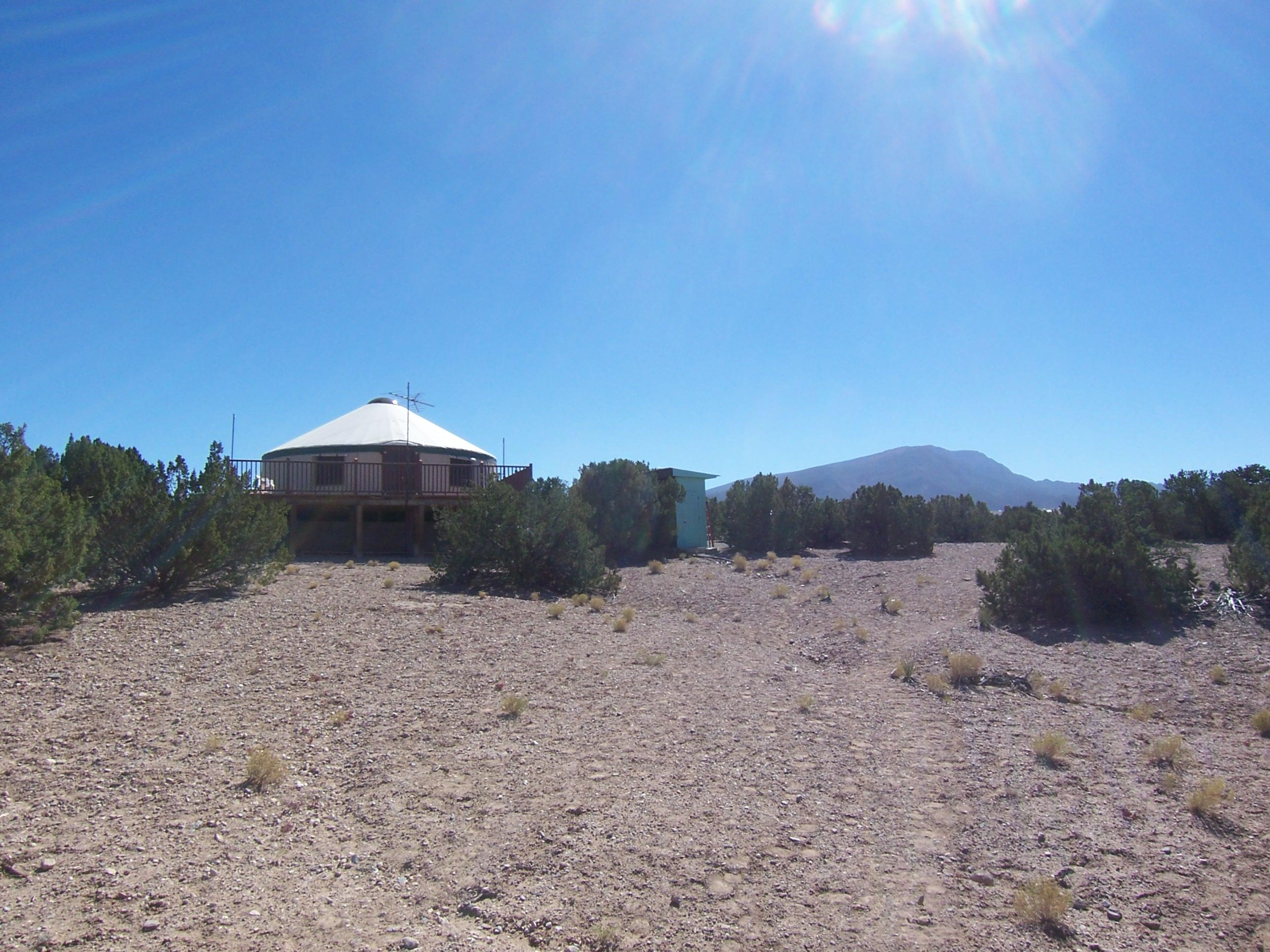 UNIQUE GETAWAY IN PLACITAS! YURT ON 3/4 ACRE NEXT TO THOUSANDS OF ACRES OF PUBLIC LAND! $69,000. A wonderful escape from the city that is just a 25 minute drive from Albuquerque! This property is bordered on the north & east by 3100 acres of Public Land! Plenty of room to build a permanent structure on this 3/4 acre! Dynamic structure with vaulted ceilings & skylight. This is one room that has the space for bdrm, kitchen, living & dining rm. Exterior building has composting toilet & shower rm. Beautiful deck to enjoy the serene views! Owners will consider short term REC with $15,000 down at 5% interest. Owners have an additional 3/4 acre lot (adjacent to the southwest) that they will sell for $50,000. Electric line run to the yurt is temporary, as the yurt is just a temporary structure.