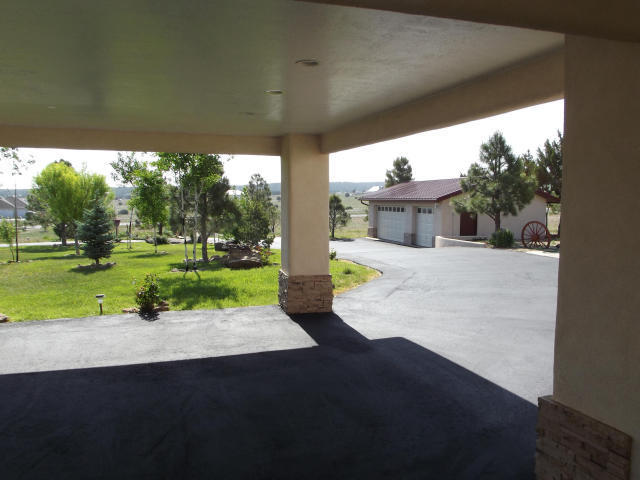 HORSE PROPERTY/ MOUNTAIN LIVING. LIVE  THE DREAM! Bring your cars and hobbies w/ 13 Car gar. plus shop all here on 6  acres with 5 structures! Paved driveways, RV space w/hookups. 5 car carport.  7000 sf of residence and guest house + game room. 2 acres of the 6+ is deeded separately and has a 4000 sf Barn. How about a Barn Home for an additional guest house, or a sound stage? Private park like oasis with lush lawns & 100's of trees and bushes, garden, & greenhouse. Perfect for wedding venue! Many have tied the knot here! Main house almost 5000 sf; + 1900sf game room w/built in bar. Guest house/honeymoon suite is a 1 bdrm, 1 ba w/full kith & bath. It's all here, come home to one of the finest properties in NM. Seller will consider REC/ owner financing w/appropriate  down paymen