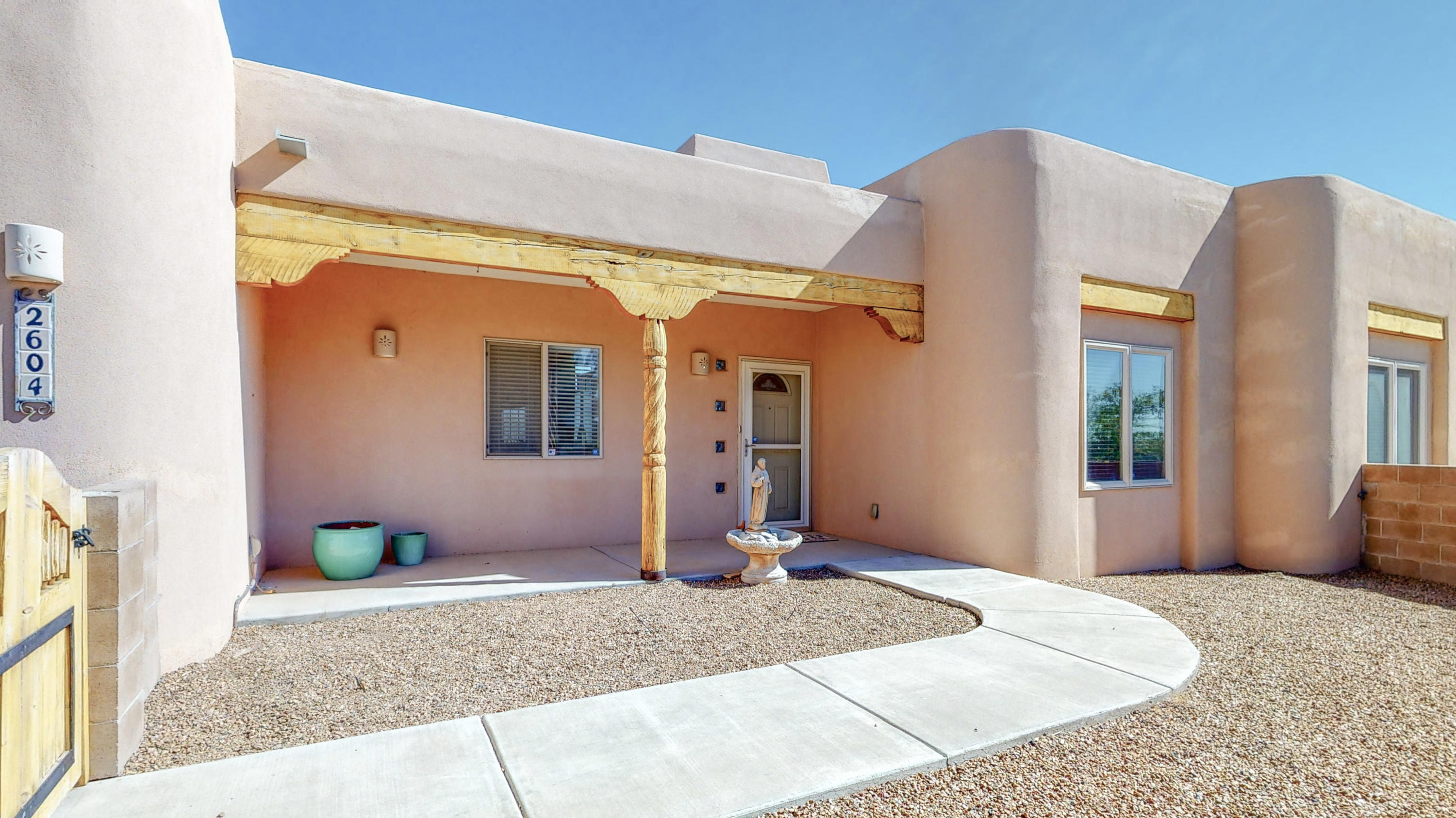 Beautiful custom home on landscaped half acre in Northern Rio Rancho. Lovely courtyard entry greets you.  Tile floors, and exposed beams are featured in the great room with a wall of windows for natural light. Wonderful kitchen complete with breakfast bar, pantry and dining nook.  Spacious master with walk-in closet and extra storage has door to the covered rear portal.  Courtyard wall in the back, too.