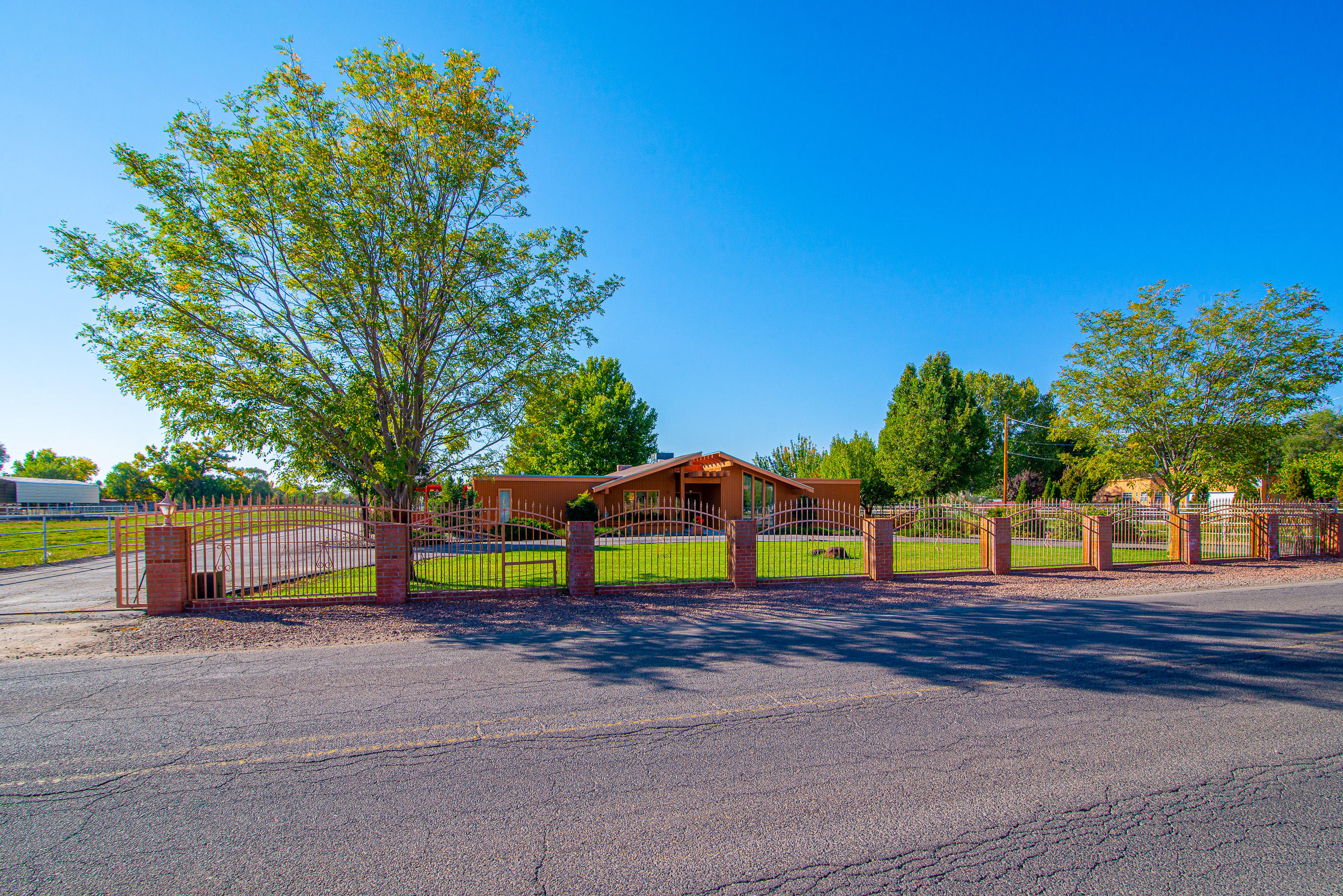 Stunning custom built home in the heart of Bosque Farms. Pride of ownership shows in this custom redwood home complete with 1,600 sq ft barn, 1,200 sq ft casita and green house on 2 acres. This unique property has been impeccably cared for and there's beauty around every corner. Custom wrought iron fencing/gates, park-like landscaping, mature trees and MRGCD irrigation. Main home includes beautiful redwood walls, updated kitchen, lg master bedroom, 3+ living areas, vinyl luxury flooring, HVAC, triple pane windows w/blinds and an ADA bathroom.  Enjoy mornings in the sunroom overlooking the backyard. Casita is fully equipped w/2 lg bedrooms, LR/DR, kitchette, full bathroom and plenty of storage space. Below you'll find the barn complete w/tack room, wash room w/half bathroom, 4 stalls