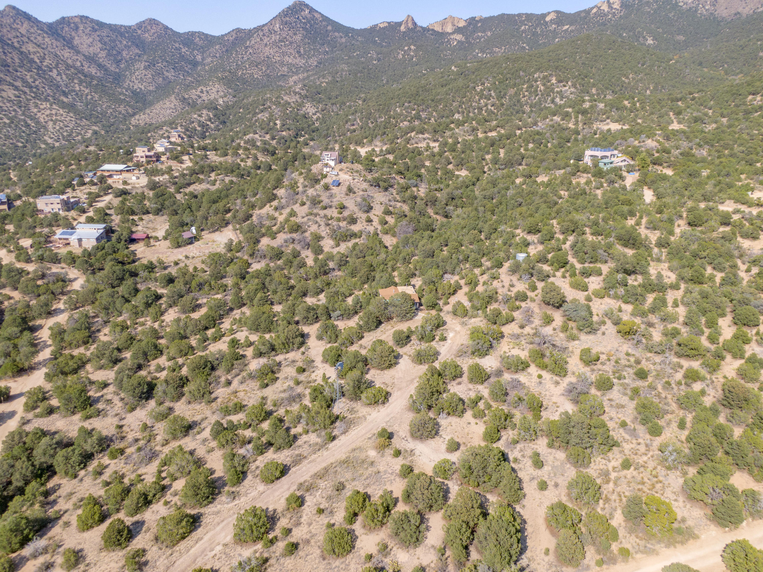 Rare opportunity to own 10+ acres of land near the la luz trail. Properties in evergreen hills are off the grid. Property is fully fenced and has beautiful views of the mountains and city lights. Pinon trees are abundant, windmill on property. Excellent location for those who value their privacy,
