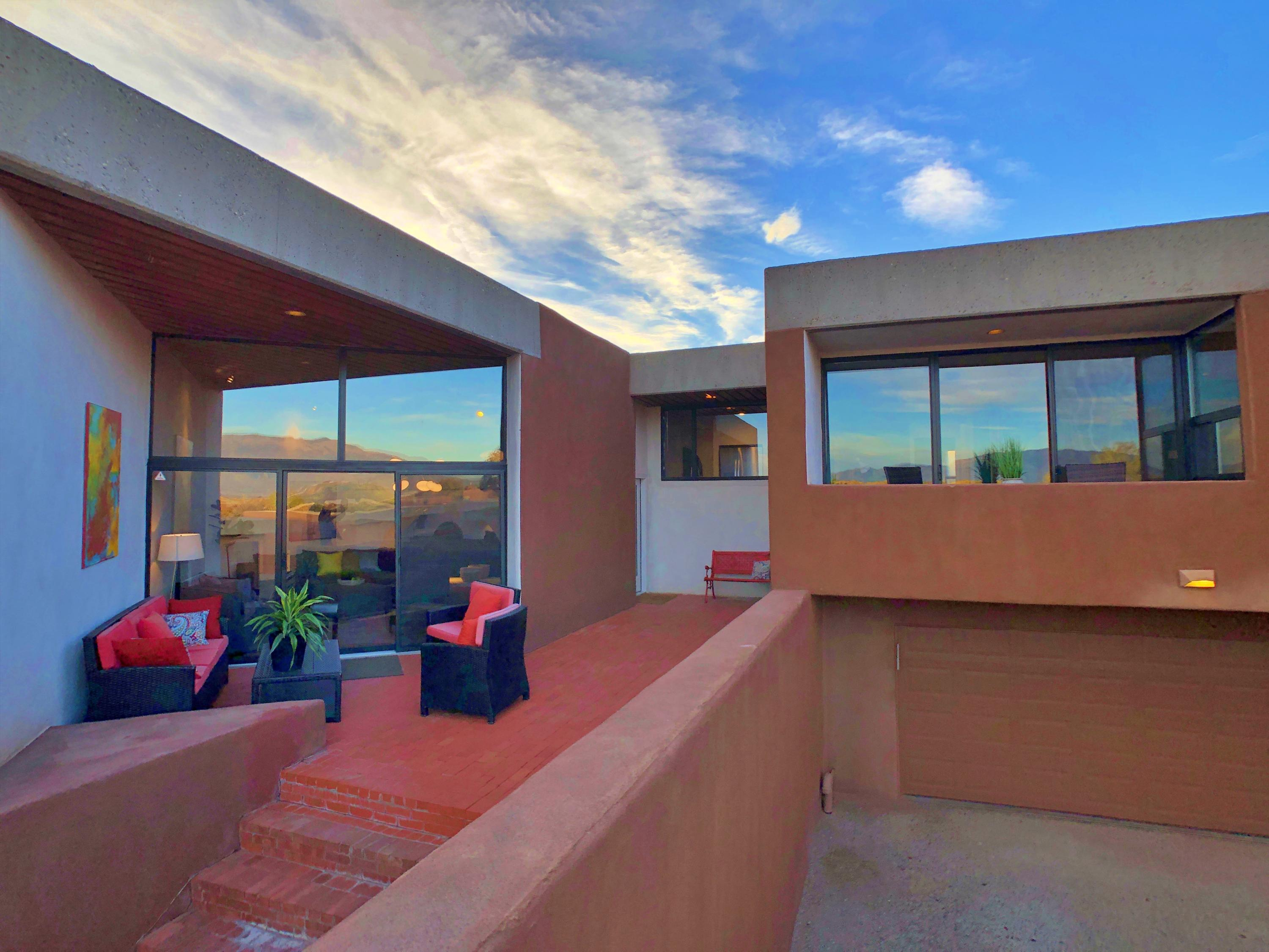 Luxe Westside townhome along the Rio Grande Bosque has stunning views & is surrounded by 5 acres of gardens & greenspaces. See both 3-D Virtual Tours! Built by renowned Architect Antoine Predock, the striking all-adobe La Luz community relishes its privacy & celebrates the surrounding space. 6 Tennis Ct NW is the embodiment of all that: it boasts one of the largest floorplans with 2 private courtyards & a sweet east-view balcony. More to love: generous-sized rooms, splendid hardwood, brick & slate floors, wood beam ceilings, arches, granite, a Kiva, numerous skylights, 2 en-suites, pocket doors & tons of storage. Take an elevator ride to the fabulous lower level home theater room--the space also includes a separate yoga studio/home gym/extra guest area--with 3/4 bath. Come see this place!