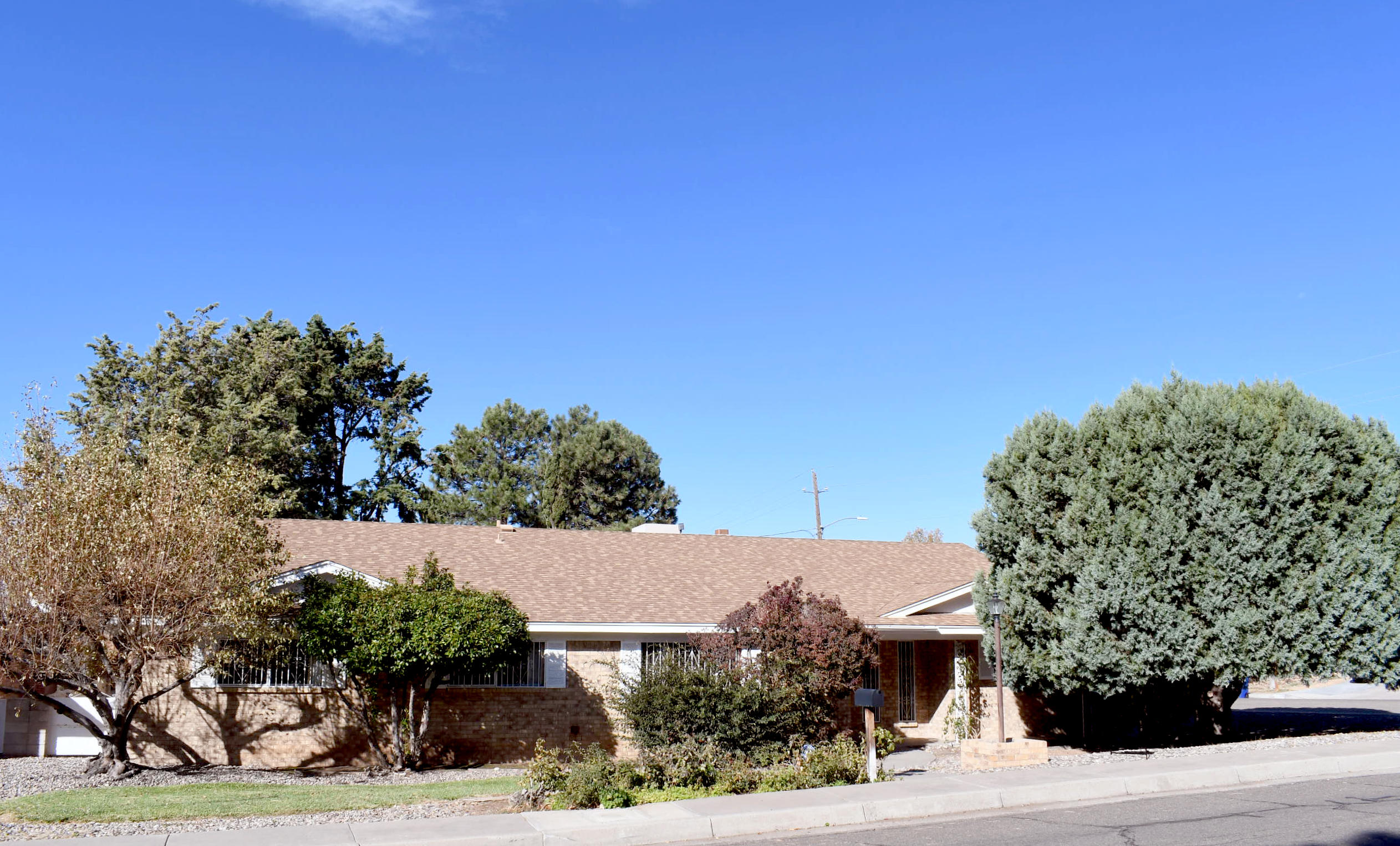Centrally-located and sitting on a beautifully landscaped corner lot, this charming  custom-built home offers a flowing, functional floor plan perfect for family living and spending time with friends.  Featuring a formal living room, dining room with built-in hutch, breakfast room, large paneled family room with built-in bookcases and cozy fireplace.  Storage galore throughout the home.   Four generous sized bedrooms, three of which have walk-in closets.  The master suite has a separate bath, large private shower, and a sit-down vanity.  The kitchen flows into the breakfast room.  Oversized utility room with folding area, storage, and .50 guest bath.  Finished, oversized two-car garage.  Enjoy outdoor living with rear covered patio, fruit trees, grape arbor, shade trees, bushes and roses.