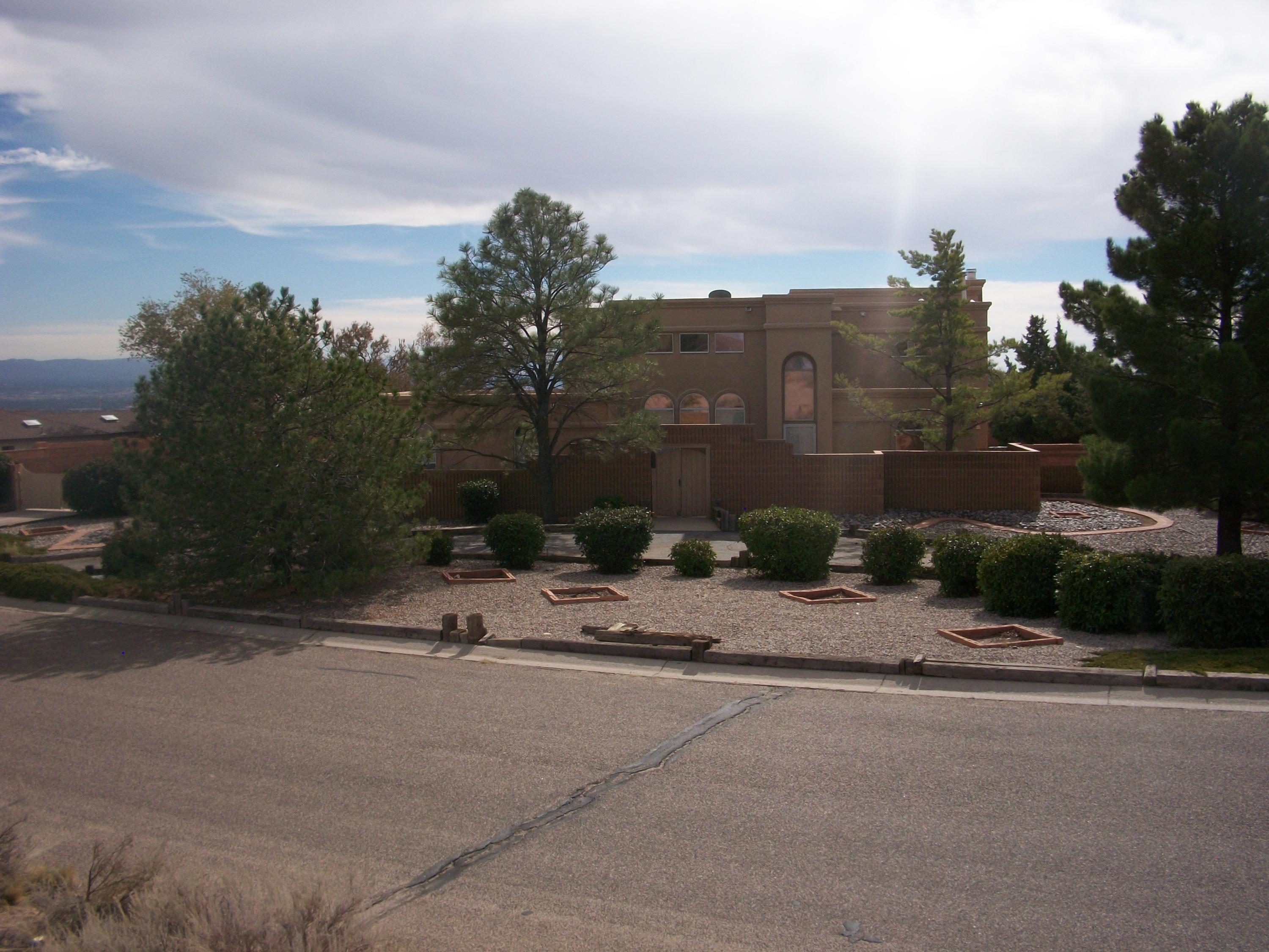 Over 2,500 square feet of eloquence! This beautiful one of a kind home comes with a breathtaking view of the Sandia Mountains and Albuquerque city lights. Over 1/2 acre of mature landscaping make this home feel like your own slice of paradise. The beautiful chandelier greets you at the entrance, with over 12 foot ceilings. All three bedrooms have their own full bath with a half bath on the main floor. Plenty of room to entertain with two separate dining rooms, the 600 square foot basement makes a perfect game room. The refrigerant AC, and furnace installed April, 2020 come with a transferable 10 year warranty. The home has an optional transferable warranty on all the appliances, plumbing, electrical system, and roof for a monthly fee. Beautiful new tile inside and outside. The patio has new