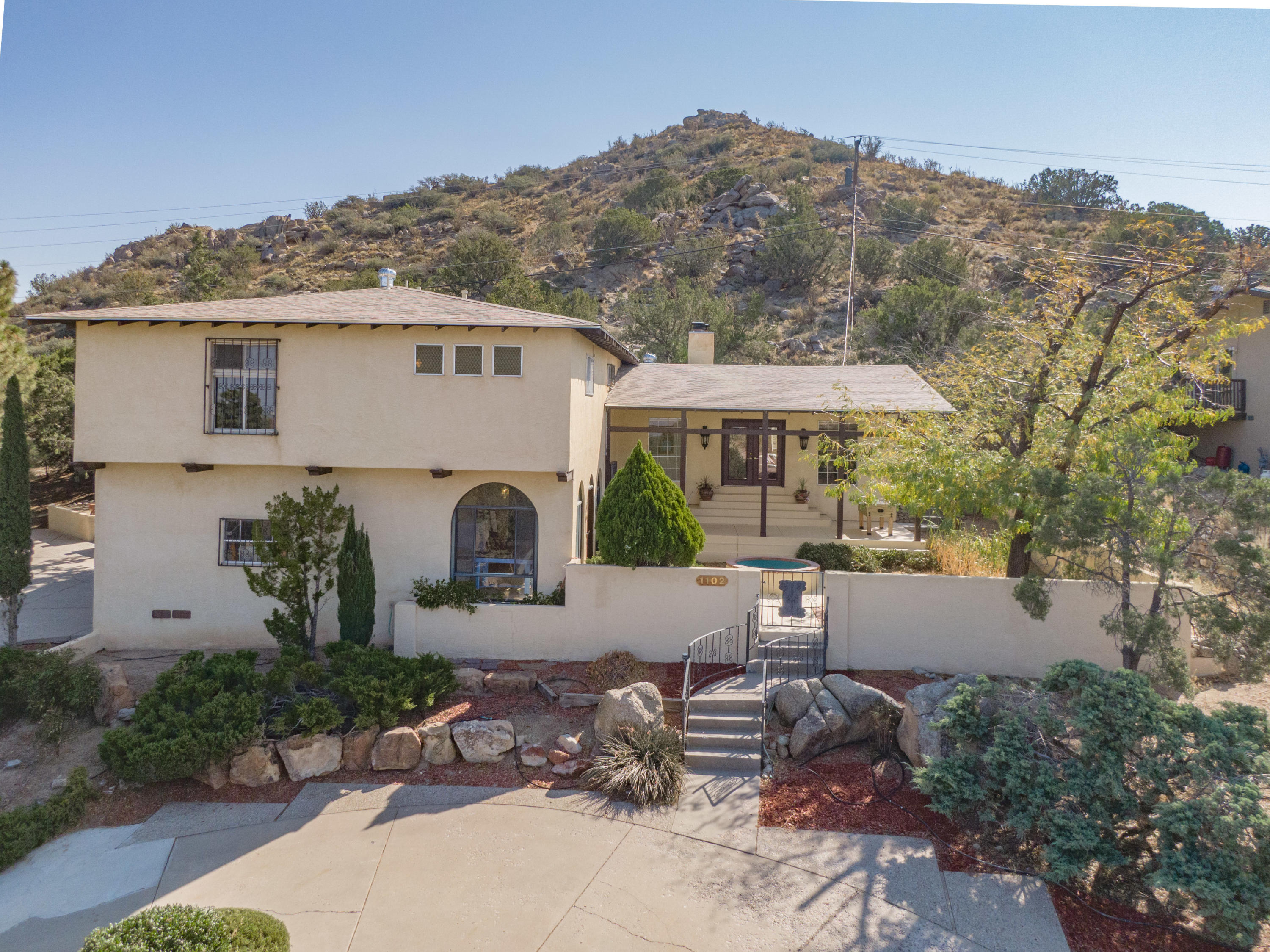 Beautiful Mediterranean style home with breathtaking views of the city and the mountains! New roof, tile and birch hardwood floors and granite and quartz countertops throughout. Large open arched windows, plus two living areas and two fireplaces. Heated sunroom overlooks the front courtyard and keeps you warm in the winter months. 2 car garage with work-shop and large storage.