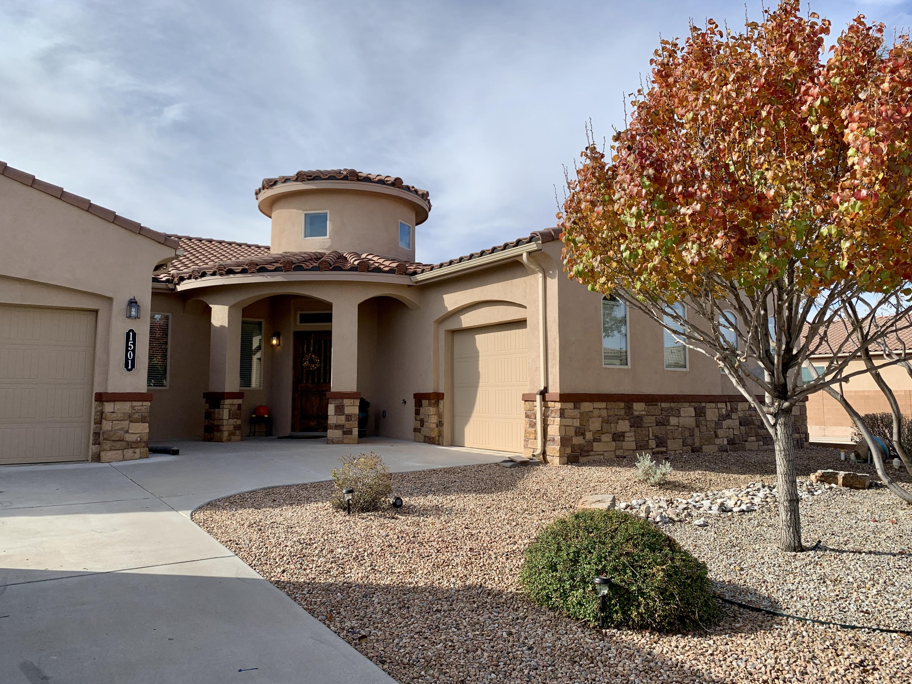 This home in the desirable Cabezon Neighborhood of Rio Rancho shines with pride of ownership. As you enter through the custom front door you will see the attention to detail throughout. The home has an open concept floor plan, with a gas log fireplace in the main living area. The outdoor back patio was tastefully and professionally enclosed with its own heating/cooling unit. The large master bedroom and master bath make a relaxing retreat for the owners. The garages have epoxy floors and the single bay garage has it own heating/cooling unit. Besides the garage space for storage, there is finished attic space with lighting to store your items. Built in bancos in the  landscaped back yard is inviting to allow you to enjoy the space.