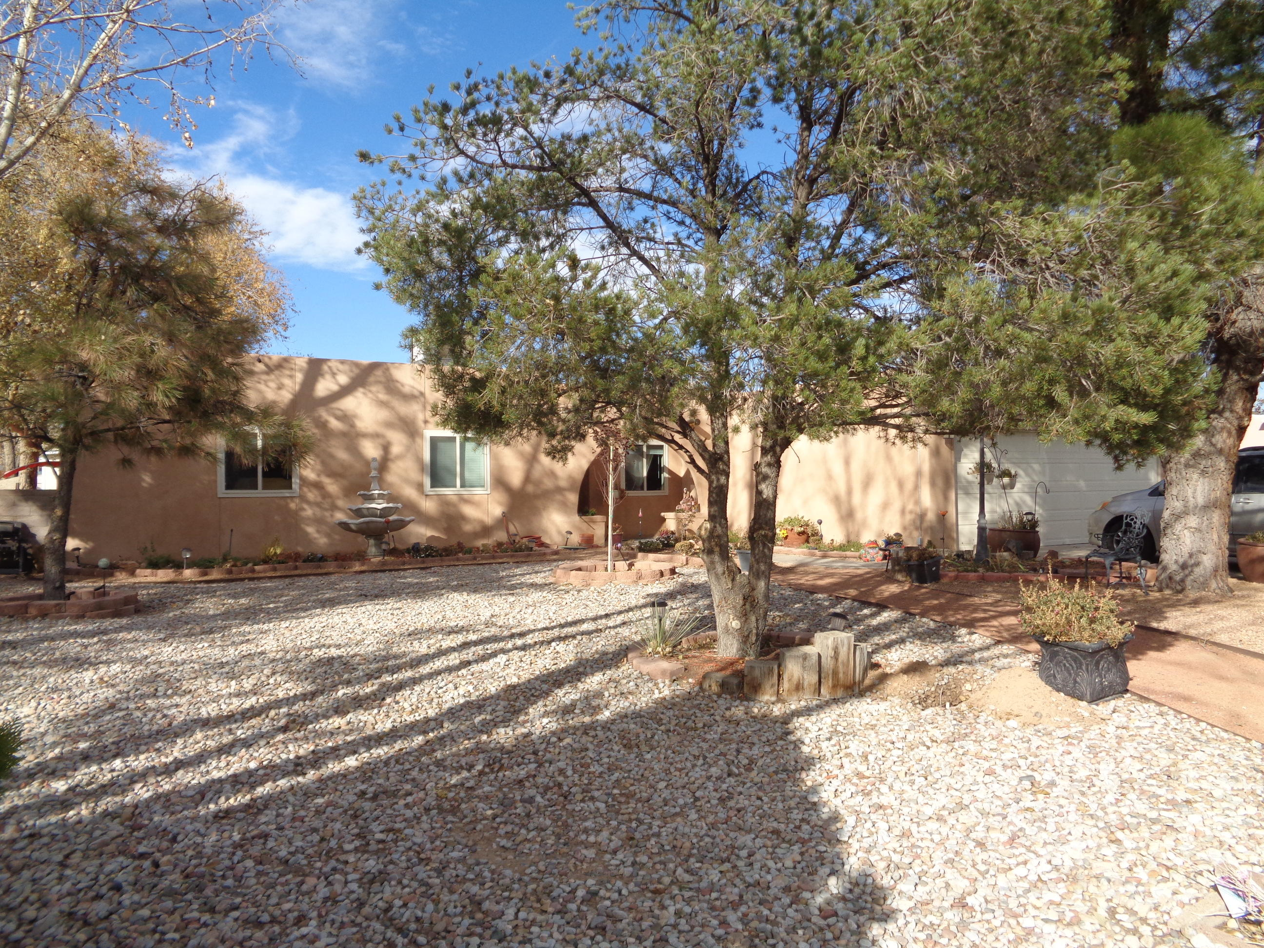 Fantabulous Pueblo-Styled Home with over 2700 SF, 5 bedrooms, 2 baths on 1/2 acre!  FP w/ insert in living room.  Island kitchen has gorgeous granite counters, loads of cabinets, stainless steel appliances and snack bar.  Large dining area plus breakfast nook.  Master suite w/ double sinks, jet tub and walk-in closet.  Garage converted into huge bedroom.  Currently one bedroom used as custom closet, but can easily be changed back.  Newer HVAC combo.  Covered patio (outdoor kitchen in progress), open patio, pond, fully landscaped w/ great lawn, trees, vines, bushes and garden.  Back yard access to 19x41x15 RV/Carport with 220 hook-up.  12x20 and 12x12 sheds w/ electricity.  Seller will consider financing with large down payment.