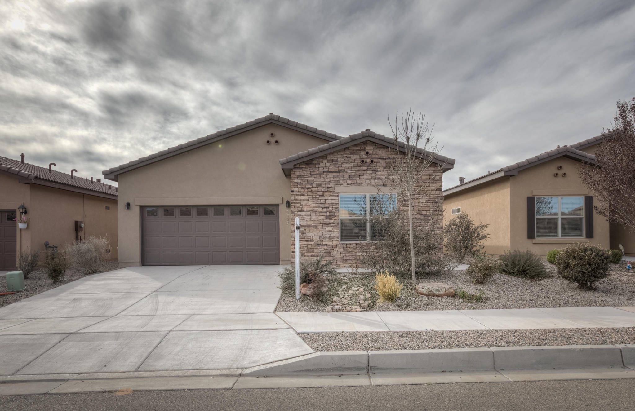 Recently Built home (2017) in the wonderful Loma Colorado neighborhood of Rio Rancho. The moment you step inside find stunning warm-hued farmhouse style laminate floors. Pass into the kitchen which is the heart of the home!  Kitchen is open and  pristine and features: Farmhouse sink, bronze fixtures & hardware, gorgeous white cabinets, stainless appliances, glass splash, & Silestone kitchen counters w/ bar.  Bathrooms have been upgraded with beautiful tile surrounds & dual sinks. The home has an amazing layout and flow and the bedrooms are all large. Laundry room is also oversized. Back patio is covered and features extended brick patio and is fully landscaped.  Home backs to an arroyo, w/ no rear neighbors, additional privacy, STUNNING views. Energy efficient/ Certified Silver built.