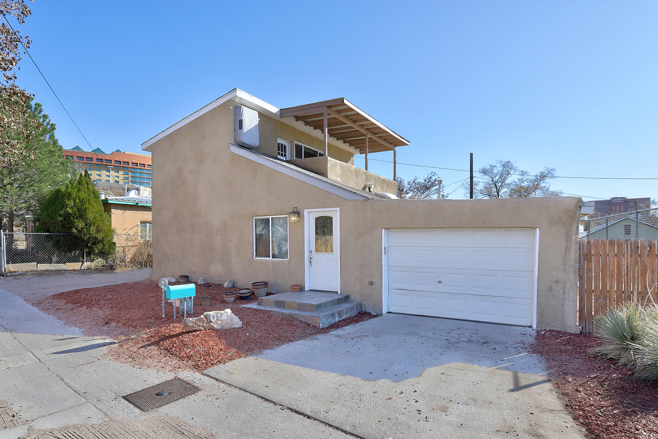 Perfect Artist partial adobe home, nestled in downtown, that takes full advantage of the city skyline views. Watch the sunset fade into the night sky as the city lights begin to twinkle for you from the second story primary bedroom balcony. Relax into the jet tub to finish off your day. Upstairs is private Primary suite oasis. Spacious downstairs with custom tile work, abundant skylights, & large kitchen with lots of cabinets & counter space. All appliances stay. Entry way with nicho opens to the greatroom for an open living & dining room perfect for entertaining.  Two downstairs bedrooms, & one has a huge walk in closet. Home has thermal windows, central forced air heat, & two evaporative coolers for zoned cooling. 3 off street parking spaces, one car garage, & completely private backyard