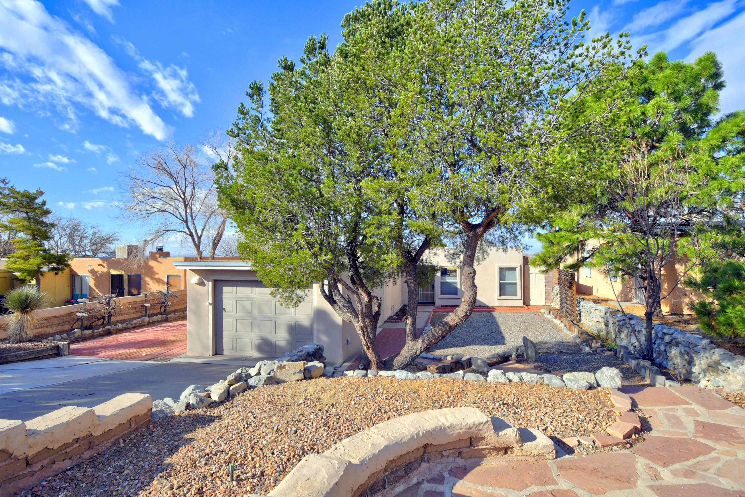 Open & spacious Casita, loaded w/extras & artistic touches. Enjoy the Panoramic sunset & city views from the Dining RM clerestory windows & backyard.  Awesome private courtyard w/covered patio/breezeway leading to the oversized one-car garage. Wood beamed ceilings & handcrafted living/dining room walls,  custom wood-burning fireplace w/seating benches.  Brick & tile floors, Stained glass, exposed adobe accents, including a full adobe wall in backyard & parts of the front yard. Granite counter tops, updated bathrooms, refrigerated-air, updated windows, 2 doggie doors. Handcrafter ceiling & walls in Office/3rd BR.  Don't miss the Garden Shed & the Man-Cave Workshop! Enjoy easy access to I-40, Kirtland Air-Force Base, nearby grocery stores, restaurants, shopping centers & foothills trails.