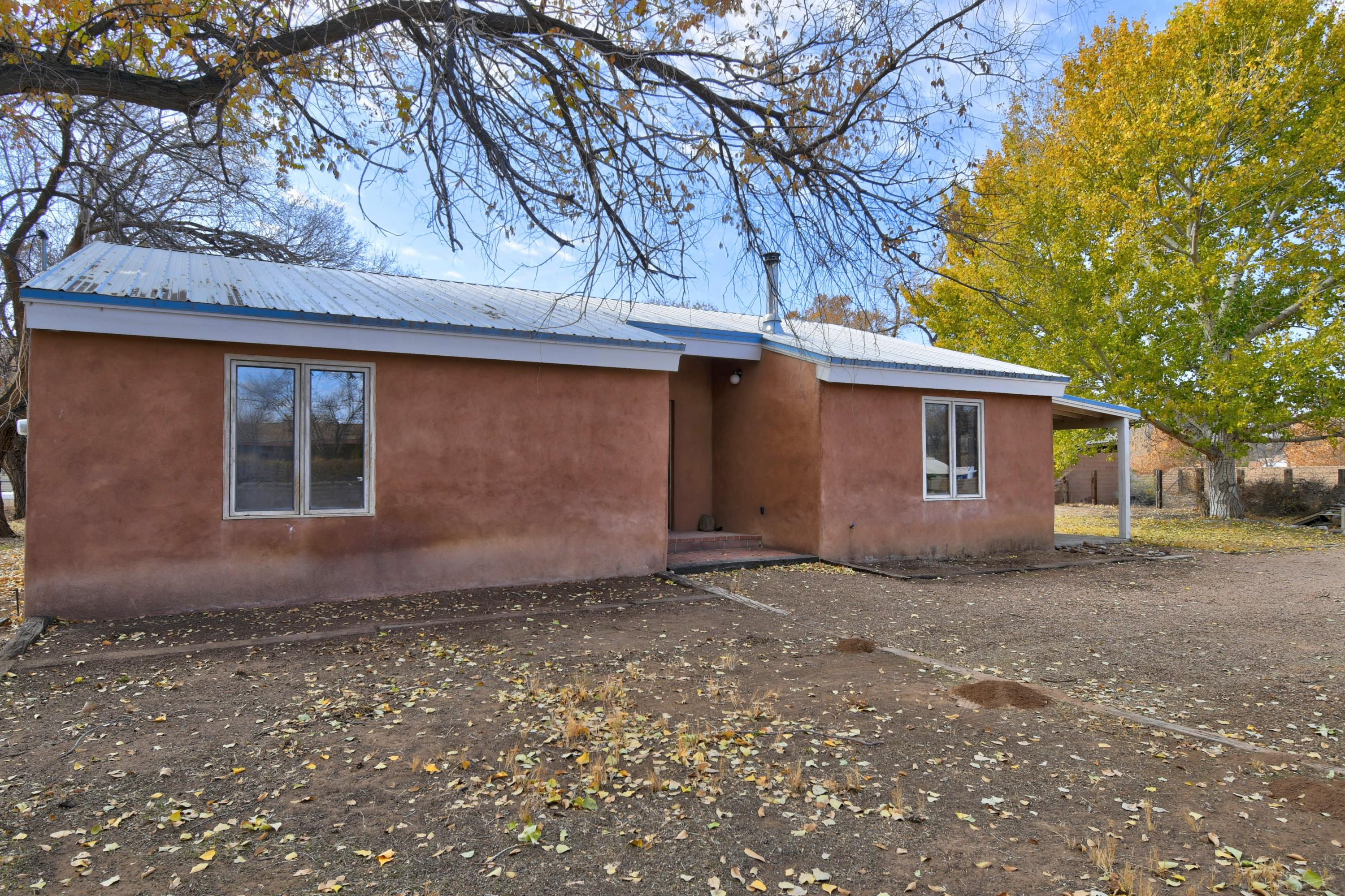 Adorable east side adobe on 1/2 acre in greenbelt.  Fabulous location to walk to Corrales restaurants, or Bosque preserve.  2 bedroom, 2 bathrooms, 2 living areas. Second living area is perfect for library or studio. Nice kitchen with dining area. Brick floors, high beamed ceilings, radiant heat, evaporative cooling.  West portal for outdoor living.  Privacy, mature cottonwoods, adobe wall on 2 sides,  2 wells, with one irrigation.  A separate great set up for horses, 2 stalls, large turn out, access to trails.  Storage building.  Room for gardening, dogs, and room to roam!  A wonderful property to call home.