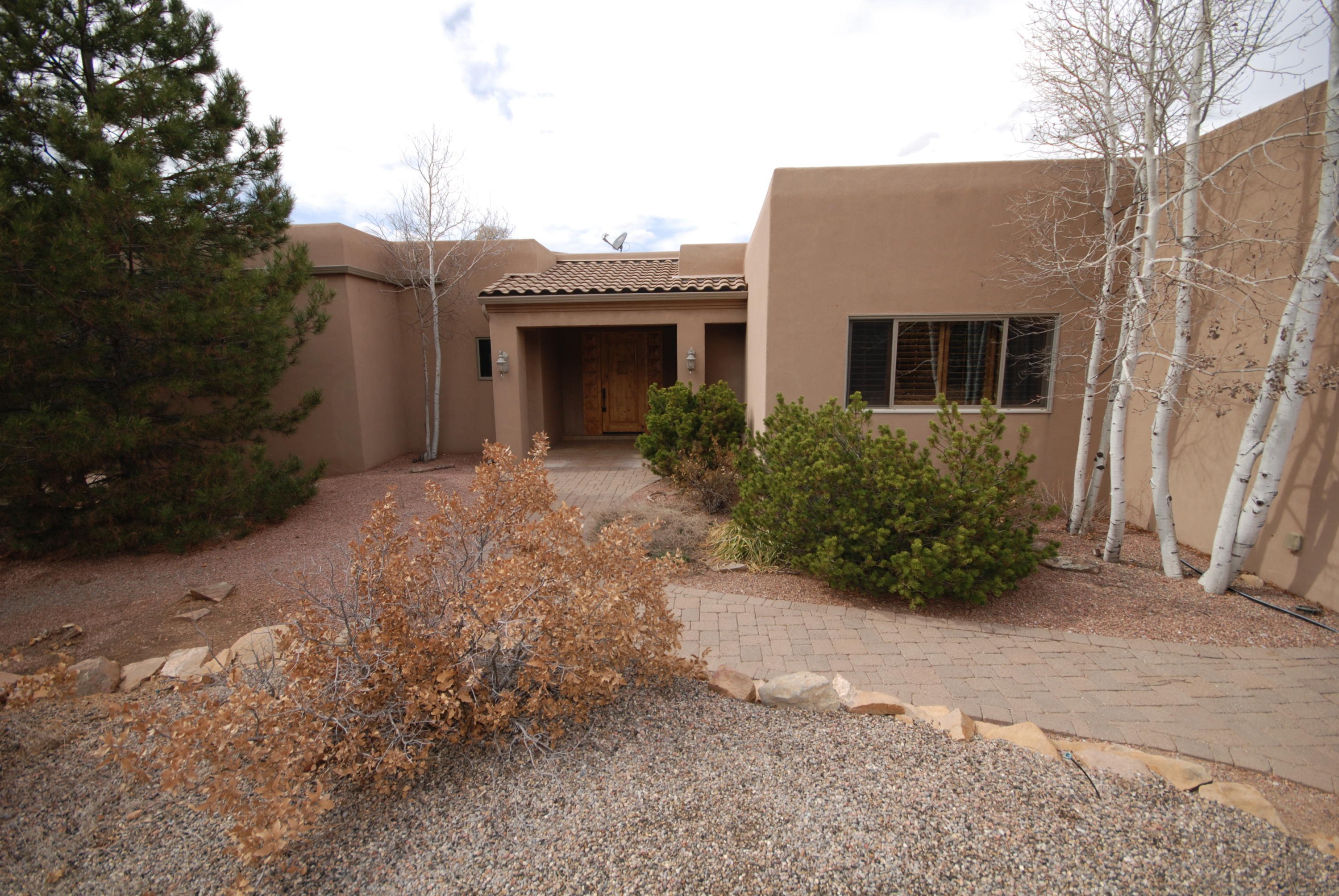 Lovely single story home on a wooded acre.  Exterior has cobble driveway, rock terraced walls and full on views of Sandia Mtns.  Covered entry leads to large great room with high ceilings and tile floors.  Cozy gas fireplace and built in entertainment center.  Formal dining room with wall of glass.  Chef's kitchen  with granite countertops, large island, 5 burner stove, double ovens, pantry, loads of cabinets.  Owner's suite has separate study or yoga room, huge walk in closet and a bathroom you could dance in.  Down the hall is a guest bedroom and bath.  On the other side of living is the third bedroom or study with a wall of glass and built in bookcases.  3/4 bath with etched glass doors.  huge covered patio with built in grill. 3 car finished garage separate workshop.