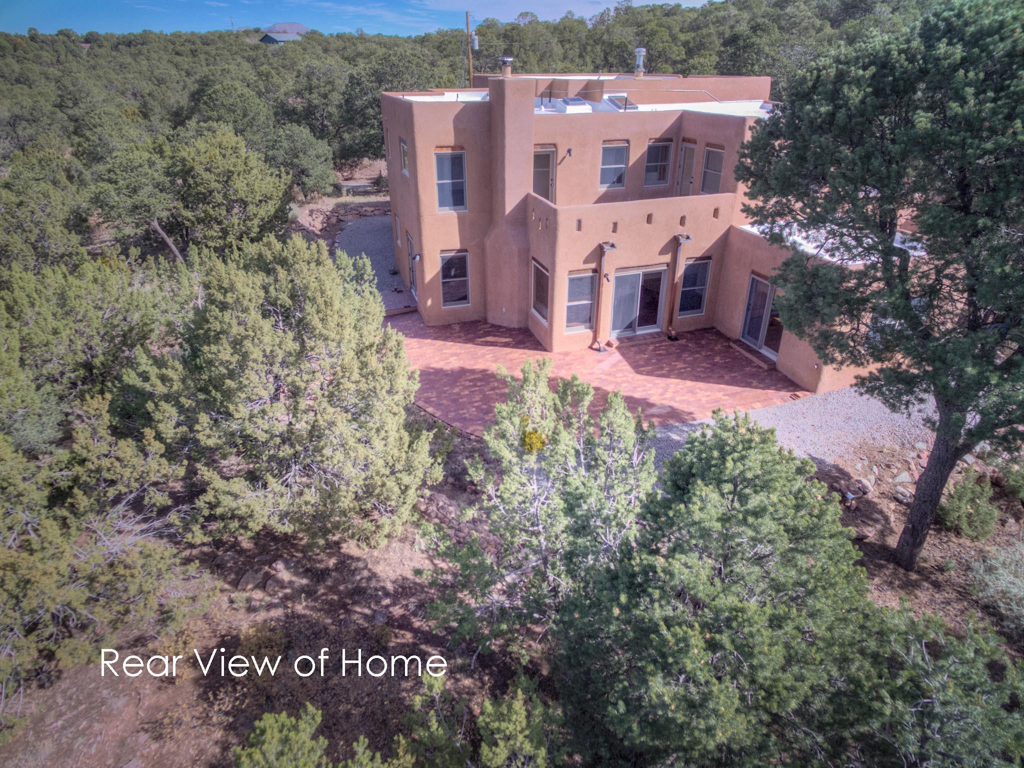Stunning East Mountain home w/ magnificent views of mountains & sunsets. 15 Min drive to ABQ. Heavily wooded 5 acres (adjacent 5 acres available).  Floorplan offers: great room & large family room (21 X 25) Garage could fit 4 cars + an additional shop area. Kitchen features an island, oversize refrigerator and freezer, hickory cabinets with Colorado slate Formica counter tops, pantry.  Great room offers abundant windows with great forest views and natural light + wood burning kiva style fireplace. Other features: high, viga ceilings, Saltillo tile flooring,  radiant heat, evaporative cooling, stucco, TPO roof, 10x12 shed. Fantastic outdoor brick patio: 2 upper decks (1 covered) offer stunning views.  Well/septic/home inspections complete.  Floorplan available. + much more !!