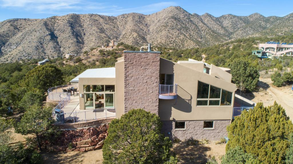 Escape to high style and unrivaled Sandia mountain/city lights views in this .9 acre wilderness-boundary home at 7000'.Green-remodeled in 2010, this 4687 sq. ft. home has it all:  vaulted wood ceilings, big glass, teak floors, fireplace, granite counters, cherry cabs - hiking trails! The practical is here too - huge finished garage, organizer closets galore, Energy Star fixtures, radiant heat, tankless water heater, 6.25 kW solar array, new roof and lithium batteries in 2020.Relaxed elegance and character on all 3 levels; 3100 sf solarium entry level w/ Mbr suite, 2 Br, 2 full baths, huge kiva office; 400 sf loft w/ 1/2 bath and Juliet balcony; 1200 sq. ft. walk-out 1-Br apartment w/ upscale open plan kitchen/entertainment/sunroom, laundry, full bath.