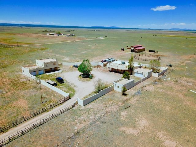 This New Mexico Pueblo Style Estate is a horse property that sits on 10 acres of grassland and features 2277 sf of living space in the main house, 792 sf 2-bedroom guest house and 425 sf in a detached office and craft room for a total of 3494 sf of total living space. Horse facilities include a 40x60 barn with an upper level that measures 12x60 and a round pen. The property is fully fenced and cross fenced. The Cibola National Forest is less than 30 minutes away, Albuquerque is about 40 minutes and Santa Fe an hour.