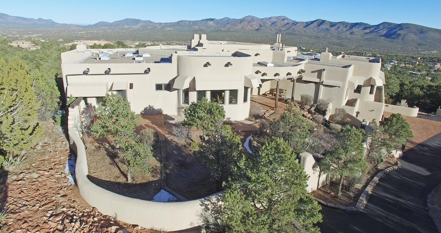 Impeccably appointed mountain top estate located in prestigious Paako Golf Course Community - just minutes between Albuquerque and Santa Fe, New Mexico.  Strategically placed atop a 9.65 Acre heavily wooded residential view lot, this one of a kind  Southwest Hacienda is a masterpiece of classic Old World  character blended with  vintage SW elegance.  Unequalled, over-the-top construction  components provide structural integrity & energy efficiency benefits - long before ''green'' construction was a ''thing''! From footings, to foundation, to framing  & roofing  - and everything in between - nothing but the best structural materials & craftsmanship were built into this stunning Masterpiece!  Come see this mountain top casa - where laid back NM lifestyle meets NM style charm!  SEE MORE....