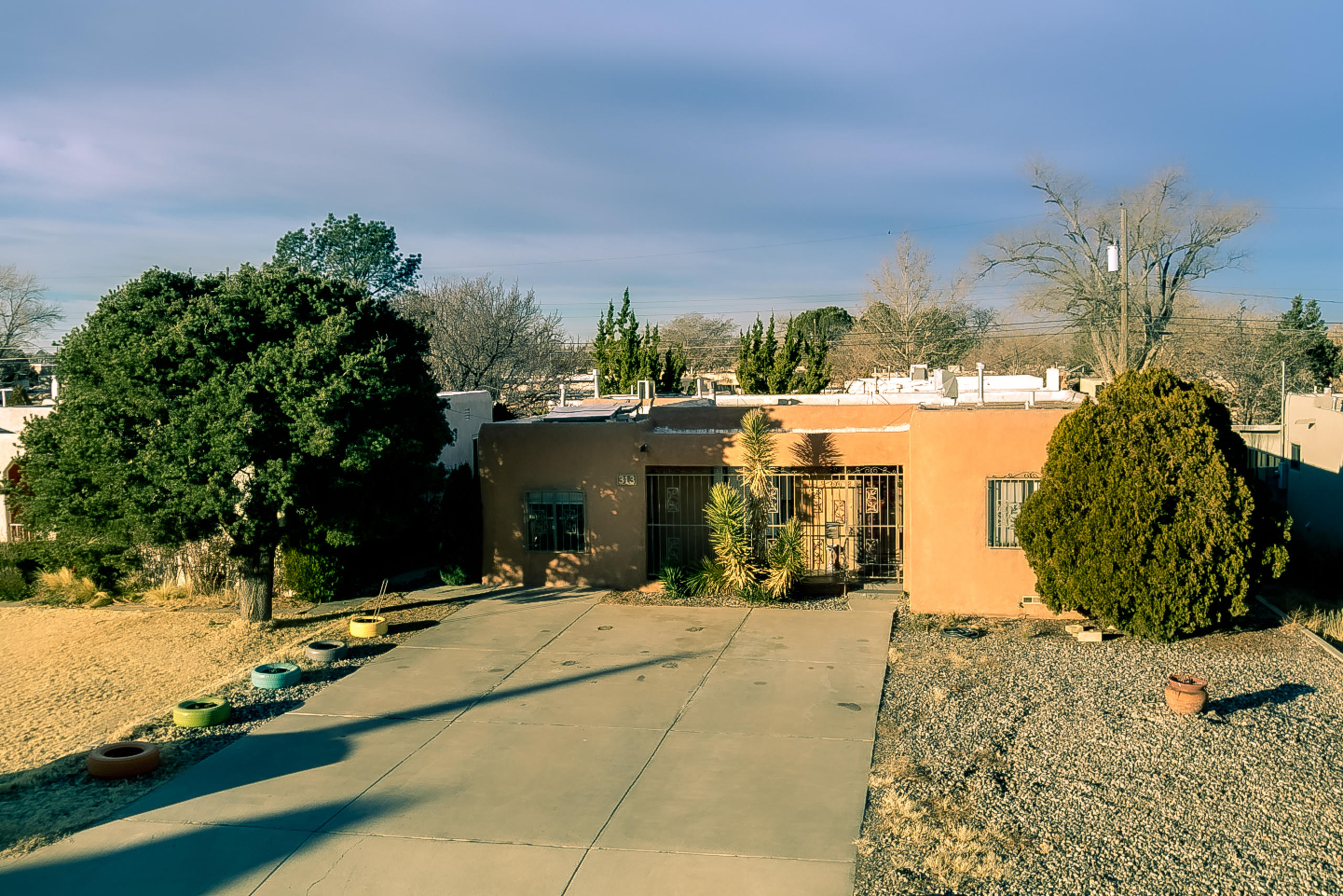 Pueblo-style home in a mature, established neighborhood that is convenient to both UNM and Uptown. Hardwood floors, coved ceilings, decorator paint colors and thermal double-pane windows. Beautifully remodeled kitchen with granite counters, subway tile and pull-out drawers. Formal living room + oversized den with cork flooring. Two bedrooms share a remodeled full bath + additional bed and bath suite with two skylights and separate outside entrance. Refrigerated air + two mini-splits. Secure, gated front porch + security bars on windows. Large backyard features covered patio with sun shade, open patio, wood fencing and storage building. Off-street parking for 3 cars. Impeccably maintained.