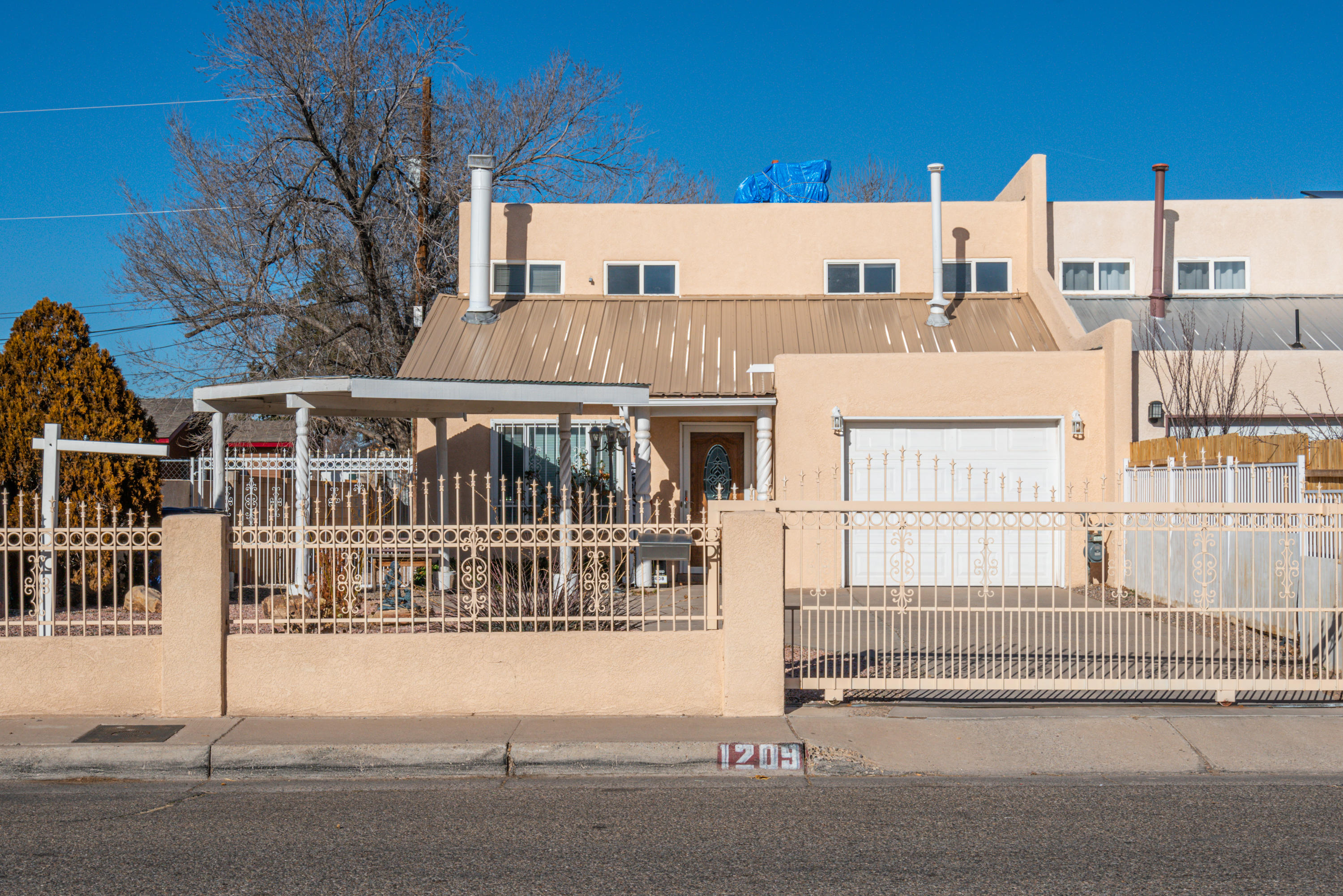 Cozy North Valley town home! Possible 3 bedrooms or 2 bedrooms/office. With living space open to the kitchen.  New Metal roof and freshly painted throughout the home. Separate carport in addition to garage.