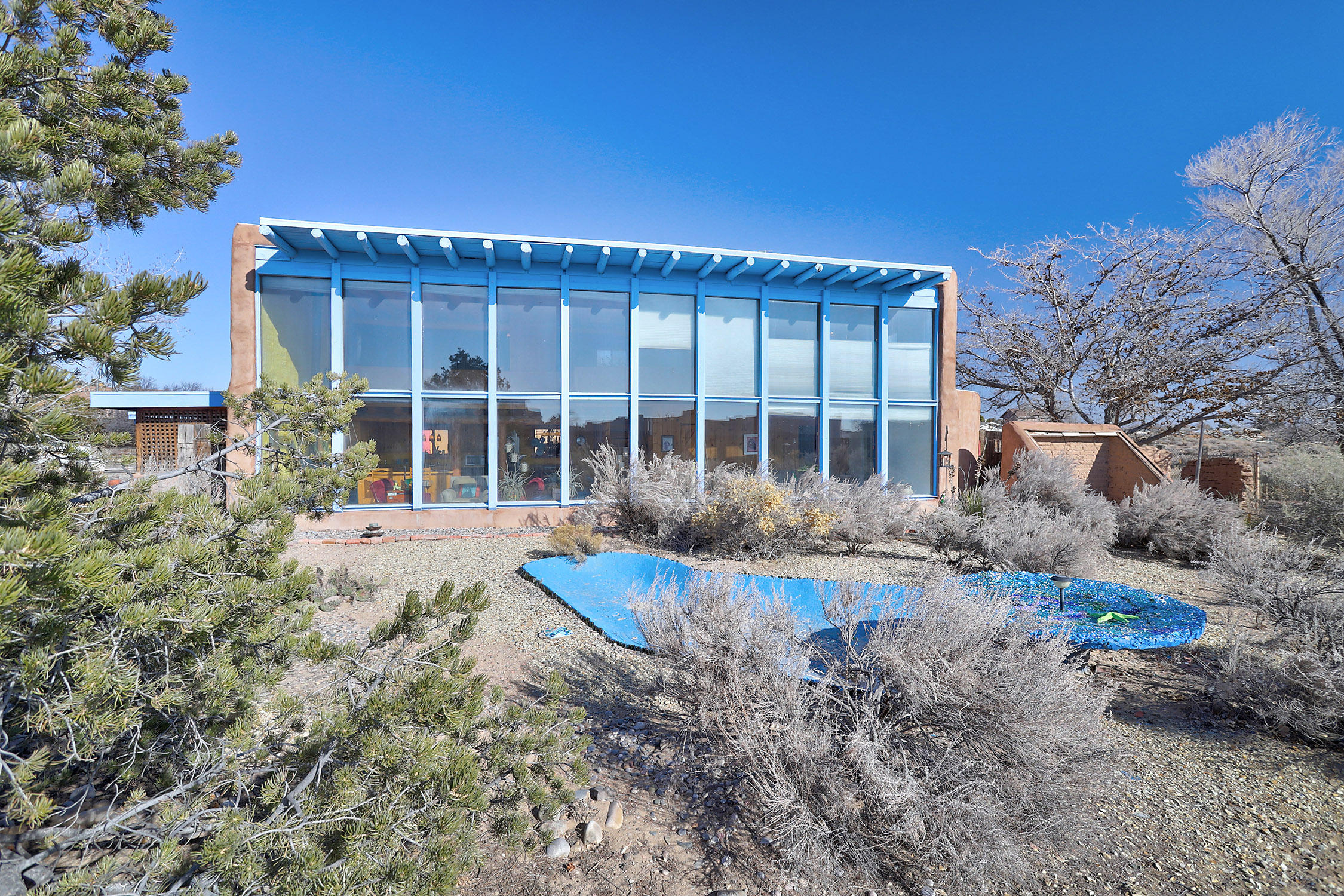 This iconic, authentic New Mexico, passive solar home boasts spectacular views of Sandia mountains & the lights of Albuquerque. Designed by renown solar environmental architect David Wright this structurally impressive adobe construction home is enhanced by the coveted cul-de-sac location showcased by mature trees, colorful plantings & two-tiered fountain on the professionally landscaped lot with front and back covered patios. The grand double paned windows encompass the entire south side of home. Brick floors & window seat bancos conduct solar heat maintaining cozy, sunny environment in winter while summers remain cool and comfortable. Bold viga beams, pine and cedar doors, walls & cupboards, highlight the warm, artistic details throughout! RV parking & expansion option at rear of lot