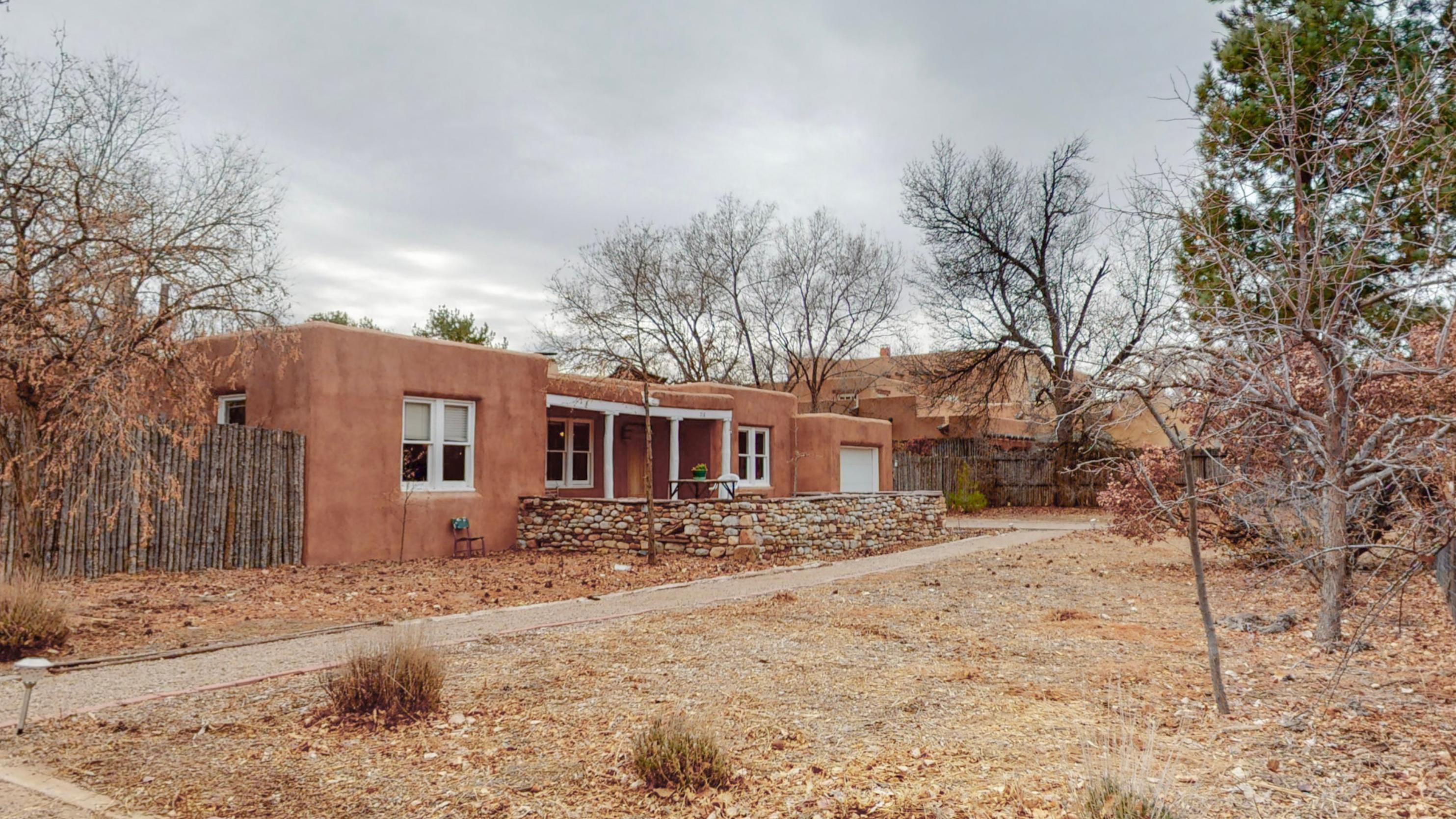Charming Pueblo style 3 bedroom, 2 bath 1557 sf home on large .76 acre lot in beautiful village of Los Ranchos. Narrow-slat oak hardwood floors, coved ceilings, sky lights, refrig AC, handmade wood plank doors, 2 remodeled baths including heated towel bar, new foam roof 2019. Pella doors bring lots of light into the kitchen. Huge fully fenced backyard has MRGCD ditch irrigation for garden, shed style barn for storage or animals, many fruit trees including apple, pear, plum & apricot.  Sellers gardened organically for 26 years- no pesticides! Need to add more space or build a casita? Lots of room on lot for more building. Low utility bills.  Seller owned solar panels provide energy for water heater & exterior insulation has been added to house.  Walk or bike on nearby trails. Come see it!