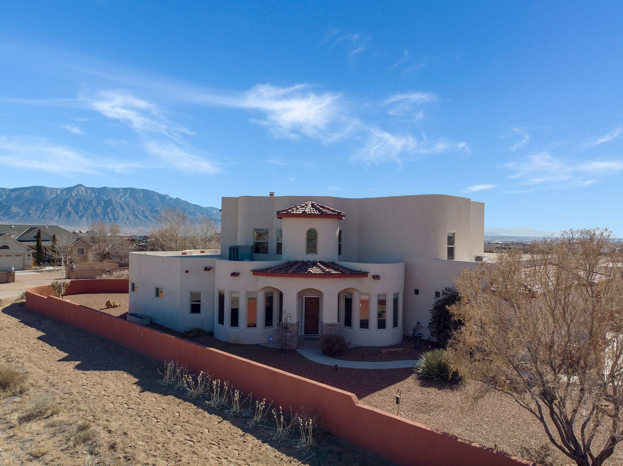 An incredible custom home on half acre lot in RR Estates. Awesome views of the Sandias & City of ABQ from two-level balcony/patio w/ trex flooring on top level. Main floor features a round turret-style foyer w/ open, large Living Room w/ Kiva-styled fireplace, nursery, large Master suite, Formal DR, 880 sq ft rec room w/ built-in bookcase & wet bar, large Kitchen w/ island, pantry & breakfast nook. Upstairs has Loft, Kids Den, & two spacious BRs. Oversized detached 3-car gar w/ lots of space for workshop & a drive-thru attached  1+ car garage. House has 32 owned hidden solar panels that lowers utilities, 10x20 covered pergola, fruit trees, 4 elevated 365-day gardens w/ built-in drip system, thermostat & heater. Two chip-sealed driveways, both lined w/ raised flower beds & so much more!