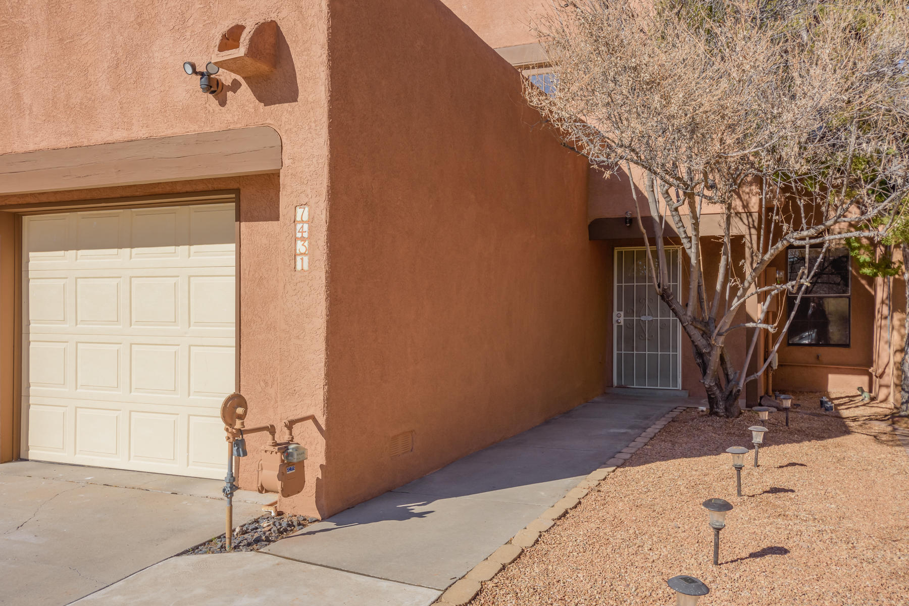 Lovely spacious Townhome in a great neighborhood centrally located in NE Albuquerque and pay NO HOA fee!  The living room has impressively high cathedral ceilings with a beautiful fireplace to match.  First level conveniently includes a bedroom, laundry, and bathroom.  This home also includes refrigerated air, TPO roof, and updated laminate flooring.  As a bonus the home includes all appliances including washer/dryer set.  MBR has access to a Balcony, full on-suite bathroom and walk-in closet.  Enjoy the year round water feature and low maintenance backyard.  You have to come see this home today because it won't last long. Shows Great!