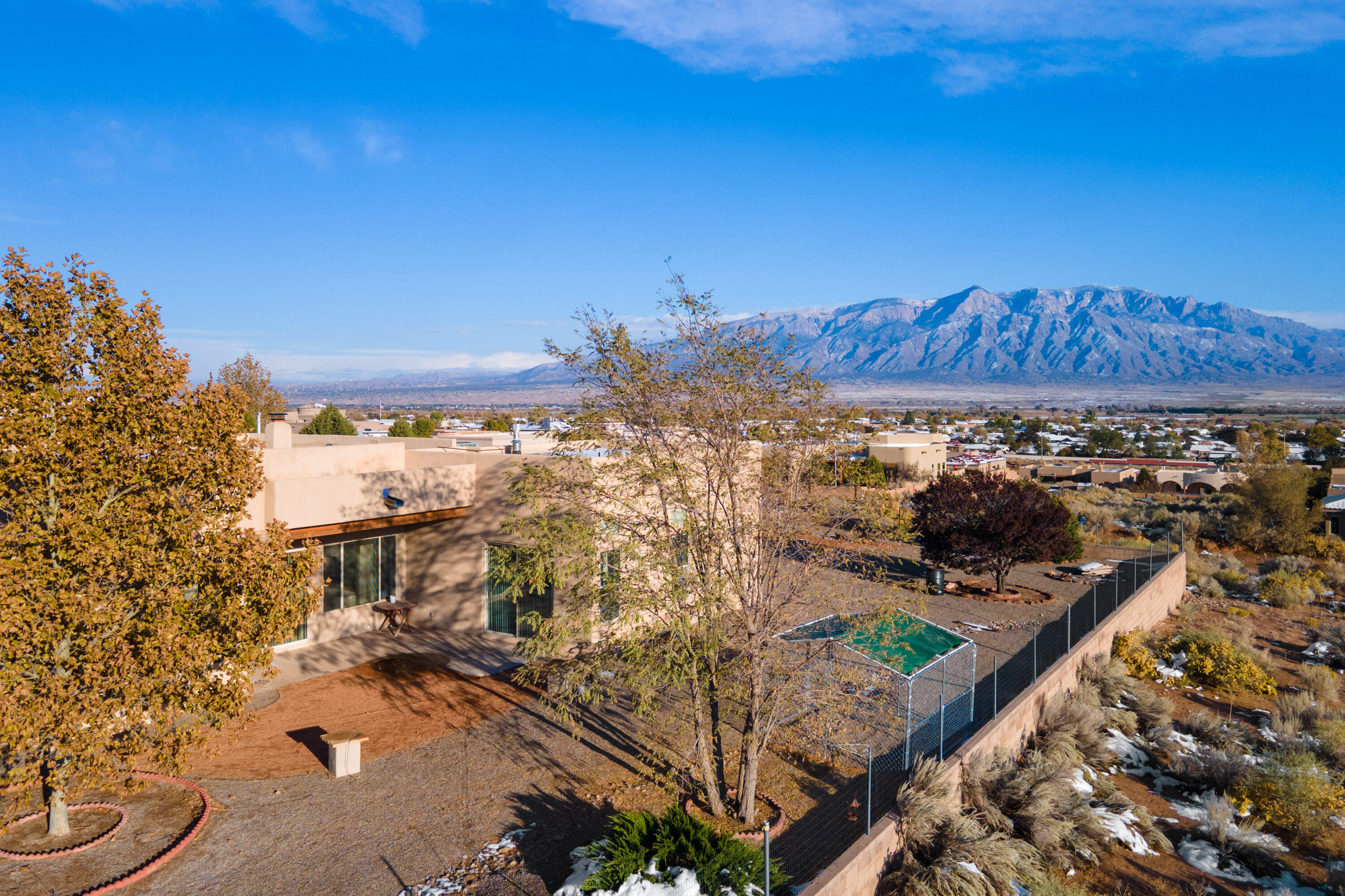 Unobstructed views of the Sandias and Albuquerque!! From the fully finished, low maintenance landscaping to the quality construction and design of this pueblo style home, you'll be impressed with the details this property offers. This home boasts a bright sunny kitchen, plenty of knotty pine cabinets, Talavera style counters with a built in kitchen desk and cooking island. It has two living areas, a kiva fireplace in the family room, that can be wood or gas, a jetted tub in the master suite, soaring ceilings and massive Viga beams. RADIENT HEAT in the floors and REFRIGERATED AIR CONDITIONING. There's a large bonus room for an office or whatever hobby your heart desires. Oh! I forgot to mention the large mostly finished separate building  of about 120 sq ft!  See this one for sure!