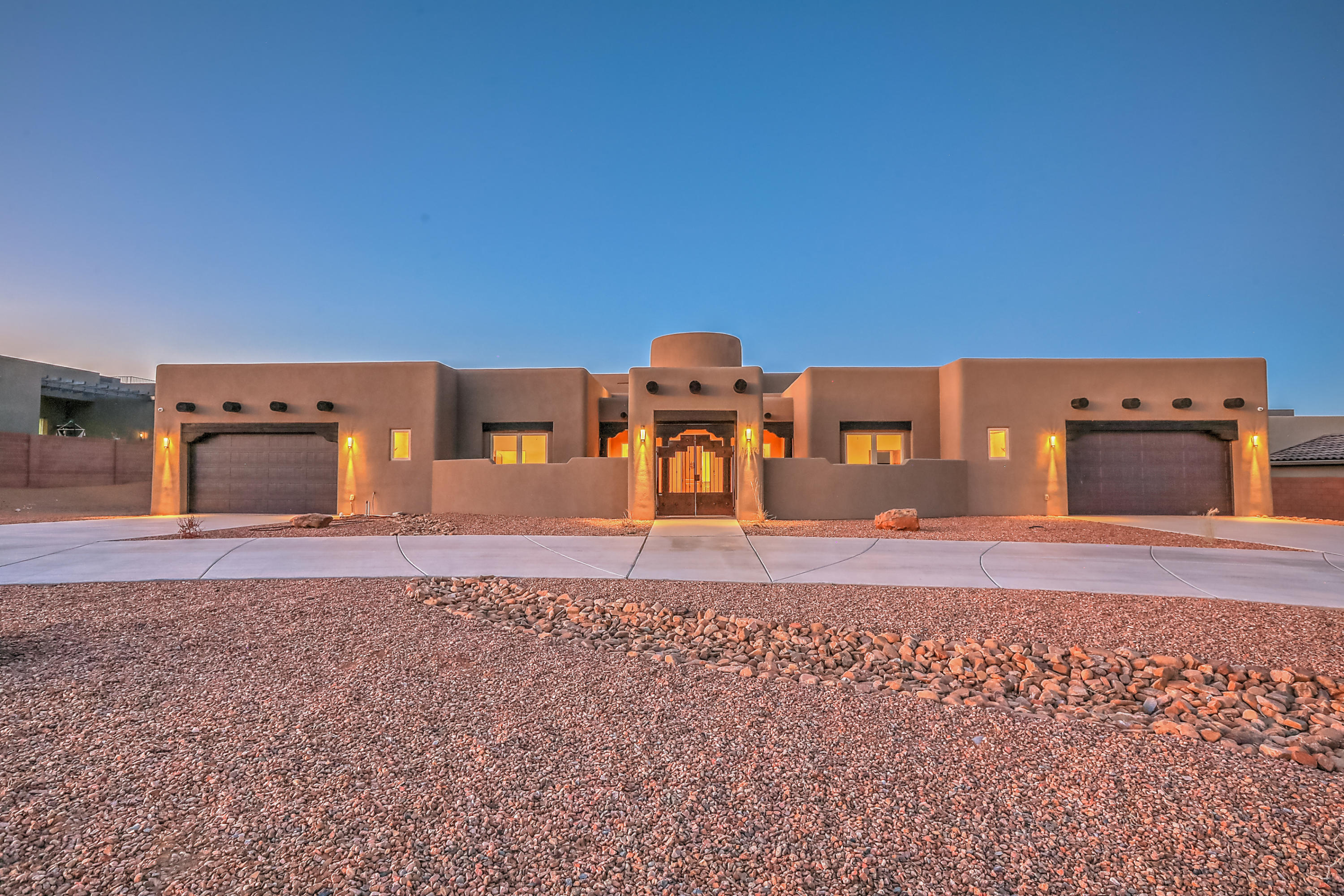 Custom designed and built by Crescent Homes, this stunning one-of-a-kind home sits on a full one-acre lot in the heart of Rio Rancho, a stone's throw from Rust Presbyterian Hospital. From the moment you enter the grand rotunda entry way with its solid wood ceiling and central fountain you experience the wonderment. Relax in front of the fire in the main living area. Everyone will want to gather around and sit at the center island in the gourmet kitchen with all the bells and whistles to be expected. Designer cabinets, granite counters, and gas cooktop.Privacy for all in the four bedrooms, all en-suite and fitted with luxurious finishes and large closets, all grand enough to each be a master. Two laundry rooms for convenience. Large covered patio to enjoy the views and party galore.