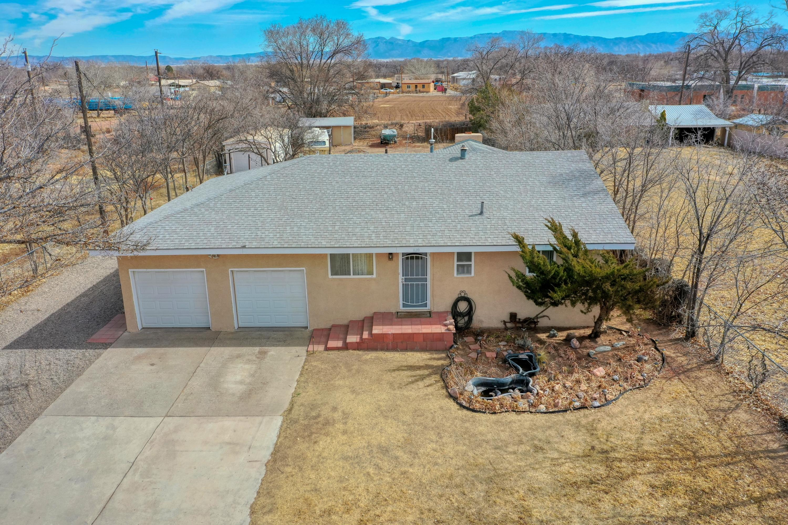 Welcome home to country living within Los Lunas village limits and close to shopping and restaurants!  This charming home sits on approximately 0.42 of an acre lot.  Refrigerated air, 2 car garage is attached and 1 detached garage in backyard.  Fully fenced with backyard access. Recently upgraded kitchen includes new oak wood cabinetry, granite countertops, Bosch stainless steel appliances and huge walk in pantry! Love the outdoors? Step outside kitchen to large covered porch leading to huge backyard, lots of fruit trees and so many possibilities for country living with ample space and outbuildings including a greenhouse!