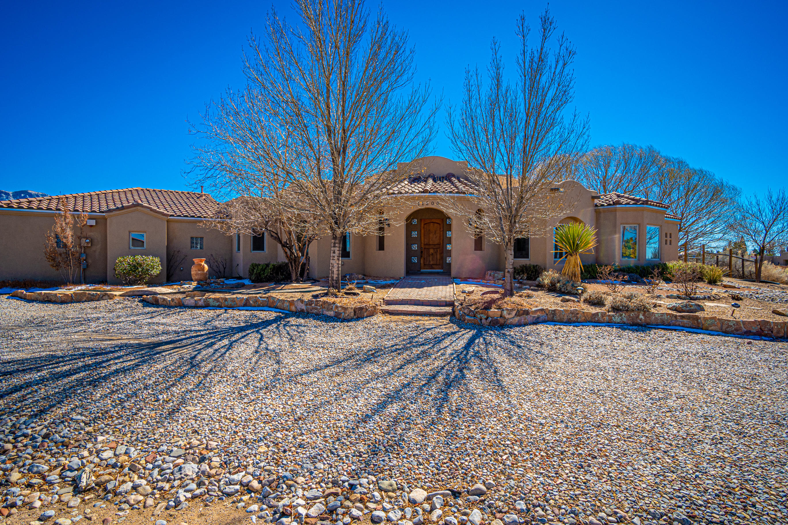 Beautiful Custom Home in North Albuquerque Acres! This one story home has been lovingly maintained by its original owners and has had many recent updates including a 1 year old TPO Roof w/transferrable warranty! With 3890 SF, this home offers 4 BR's plus an office/den, large great room with gorgeous 14ft T&G & Viga ceilings, Corbels & Viga Columns, new wood flooring (2020), Kiva FP, Formal Dining, Gourmet kitchen with island and nook, granite countertops and Knotty Cherry cabinetry w/pullouts, large pantry, DBL Oven, SS Appliances! Large Master BR has Gas FP, Master bath has beautiful tiled walk in snail shower, jetted tub,  WIC, all BR's have WIC's! Oversized 3 CG! Wonderful lush backyard has huge covered patio, built-in kitchen with gas grill & fridge and inground pool w/rock fountain!!