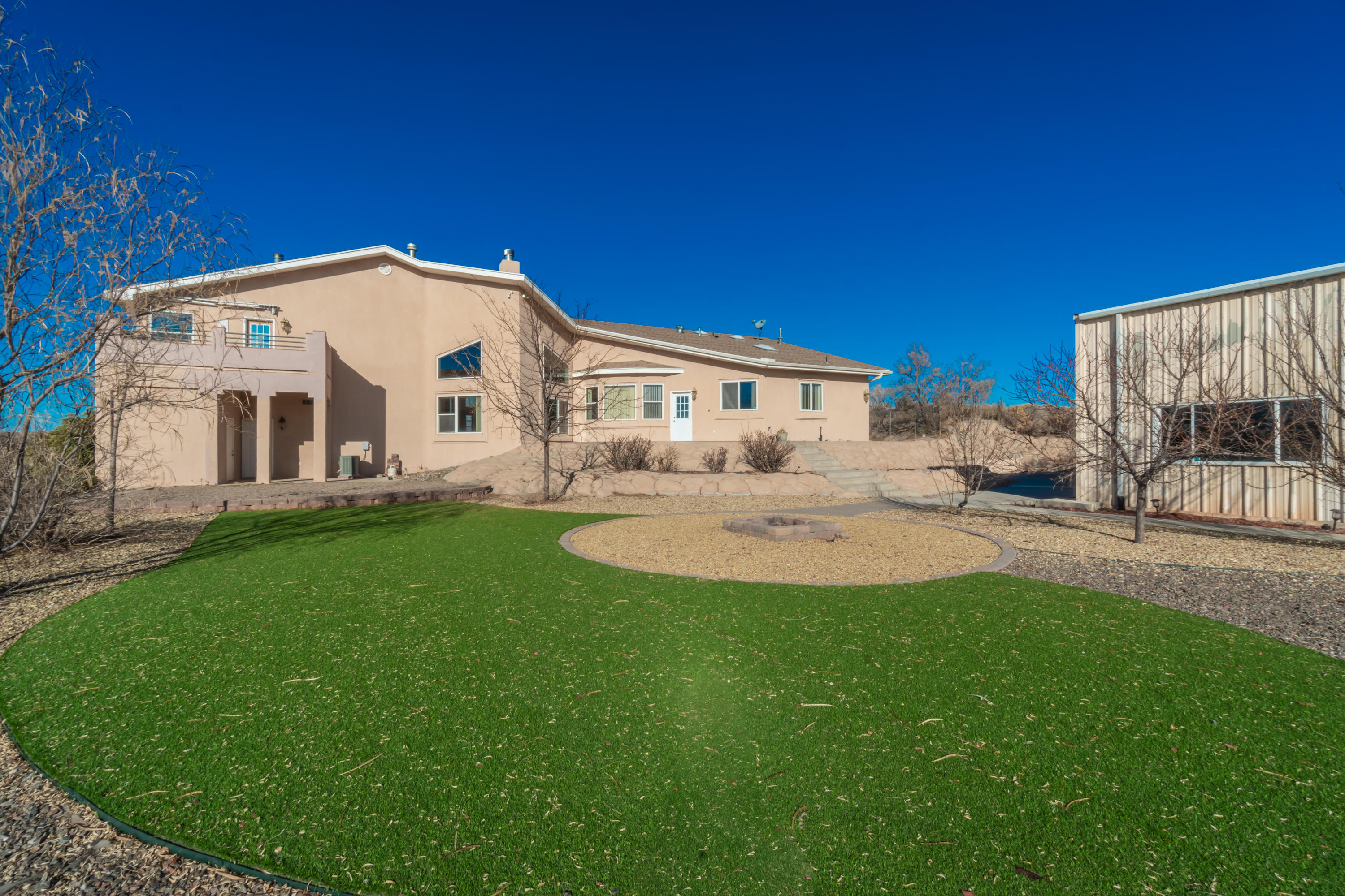 This fantastic 3194 sq ft custom built home is one of a kind! 4 bedrooms, 3 full bathrooms, and an office. The master bedroom boasts nearly 700 sq feet, double sided fireplace, and has a private balcony with a hot tub. Breathtaking views of the Sandia mountains. There is a nearly 6000 sq ft special use warehouse sitting on a fully landscaped one-acre lot. The special use building is finished with offices, living quarters, and bathrooms. This unique property offers endless possibilities to create a work/life balance.