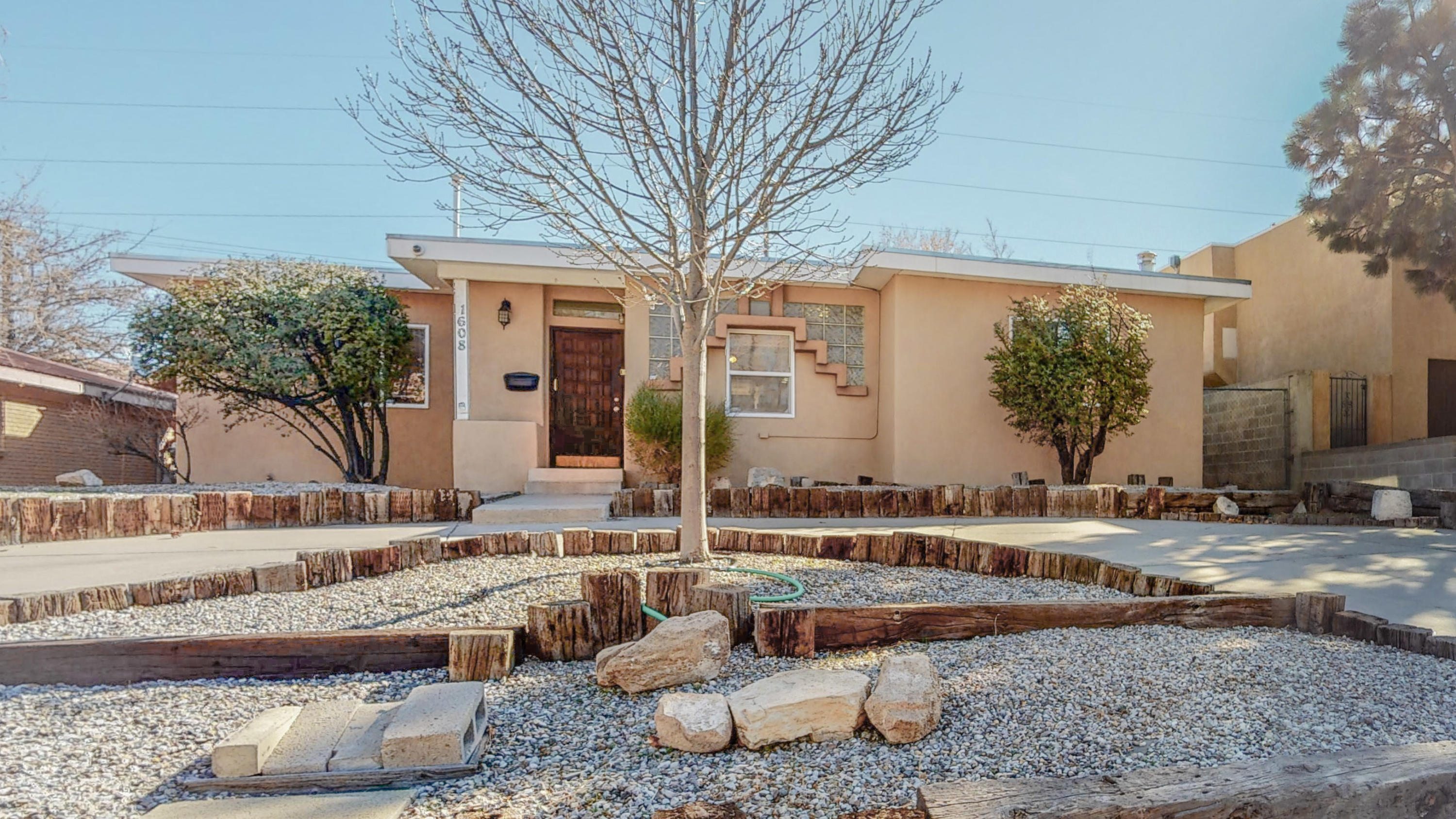 MID CENTURY MODERN W/SW CHARACTER: OPEN FLOORPLAN ON A HUGE LOT!! Awesome location near Big I, walk to Grocery!  Nearly 2000',  4 bed, 3 bath, Huge 2car gar - fits trucks. Gorgeous Wood floors were just refinished!!  +New wood-look vinyl! +  Neutral Tile in kitchen & dining.  NO CARPET!  BRAND NEW STAINLESS STEEL APPLIANCES- being shipped!  Granite tile counters, Brkfst Bar, Custom Cabinets, Pantry, Gas range.  Master Cool Evap. +Refrig/Heat combo only  in Office/Bdr. W/D  included- no warrantee.  2 en-suite bdrs plus 2 others share a full ba w/2 sinks. TPO Roof. Recent stucco work.  Large  fenced lot- w/ drive-thru back gate & attached garage.  Huge storage bldg included!!  Lg covered Patio-may not be permitted- but great shady space!  Circle Drive!  OFFERS WILL BE VIEWED Sun 2/28, 4PM.
