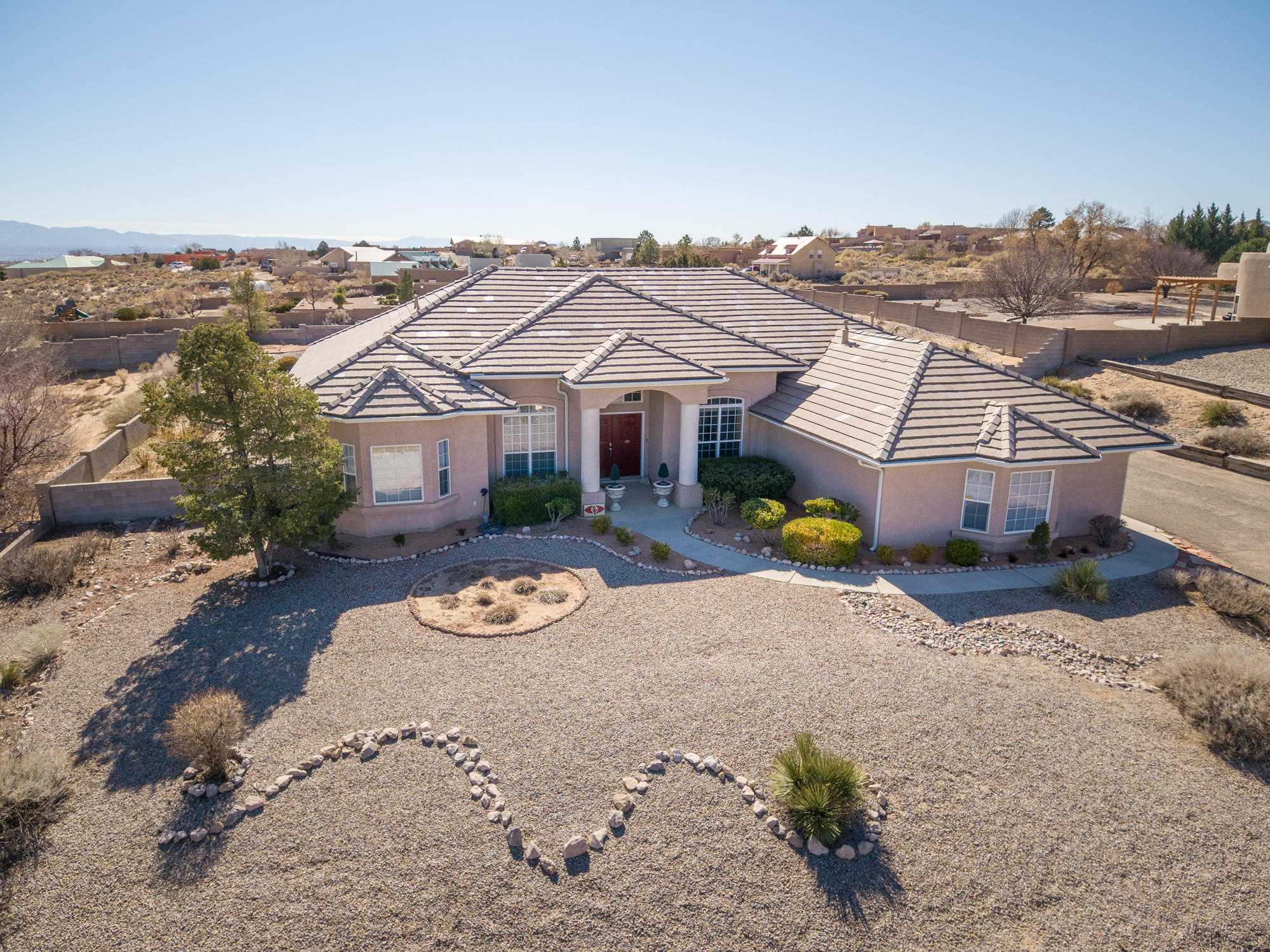 Elegant, true one story custom home in Rio Rancho Estates., with magnificent views (sweeping views) of the Sendia's on a 1/2 acre lot with back yard access. One owner home, Pride of ownership. This spacious home has soaring ceilings, light-filled rooms, two living areas, formal dining room, a well appointed kitchen with breakfast nook, stainless appliances, ample cabinets and countertops. Four generous bedrooms. Porcelain wood grain tile throughout. 2x6 Frame construction. Wonderful outdoor living spaces adds to the beauty of this home, covered patio facing east to enjoy the VIEWS of the Sandias. Must see home!