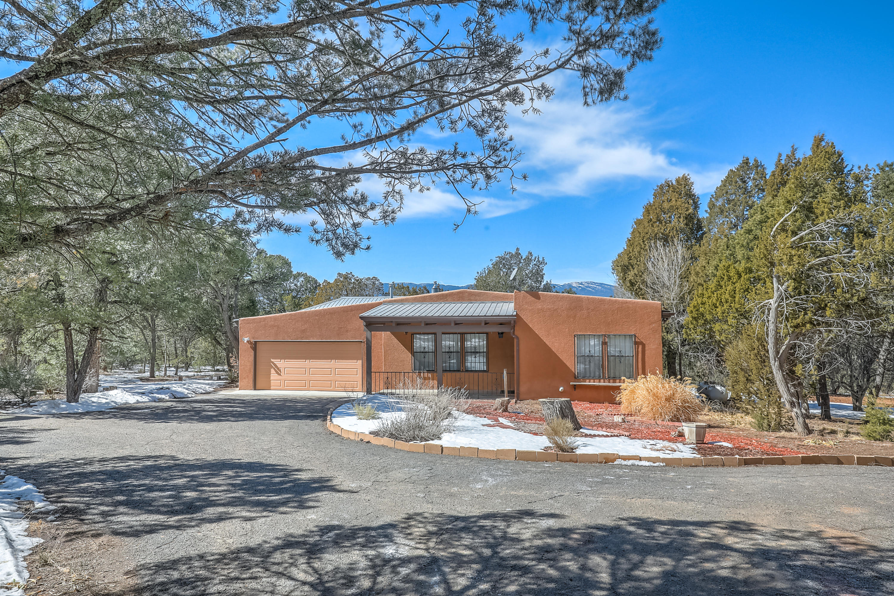 Welcome Home to your own private retreat, nestled in the pinon trees! This lovely 3 bedroom 2.5 bath home, offers a spacious great room with SW accents, beamed ceiling, wet bar and cozy pellet stove. Country Kitchen with island, separate dining room, heated sunroom, office, and large primary suite featuring a full bathroom, walk in closet and beautiful sunroom perfect for a nursery/gym/library. Sitting on 4 beautiful acres, this property also includes a 2 car finished garage and a large workshop/art studio. Fresh interior paint, new septic, newer water heater, and well was drilled deeper a couple of years ago with new pump and wiring installed. This beautiful property is ready for its new owner!