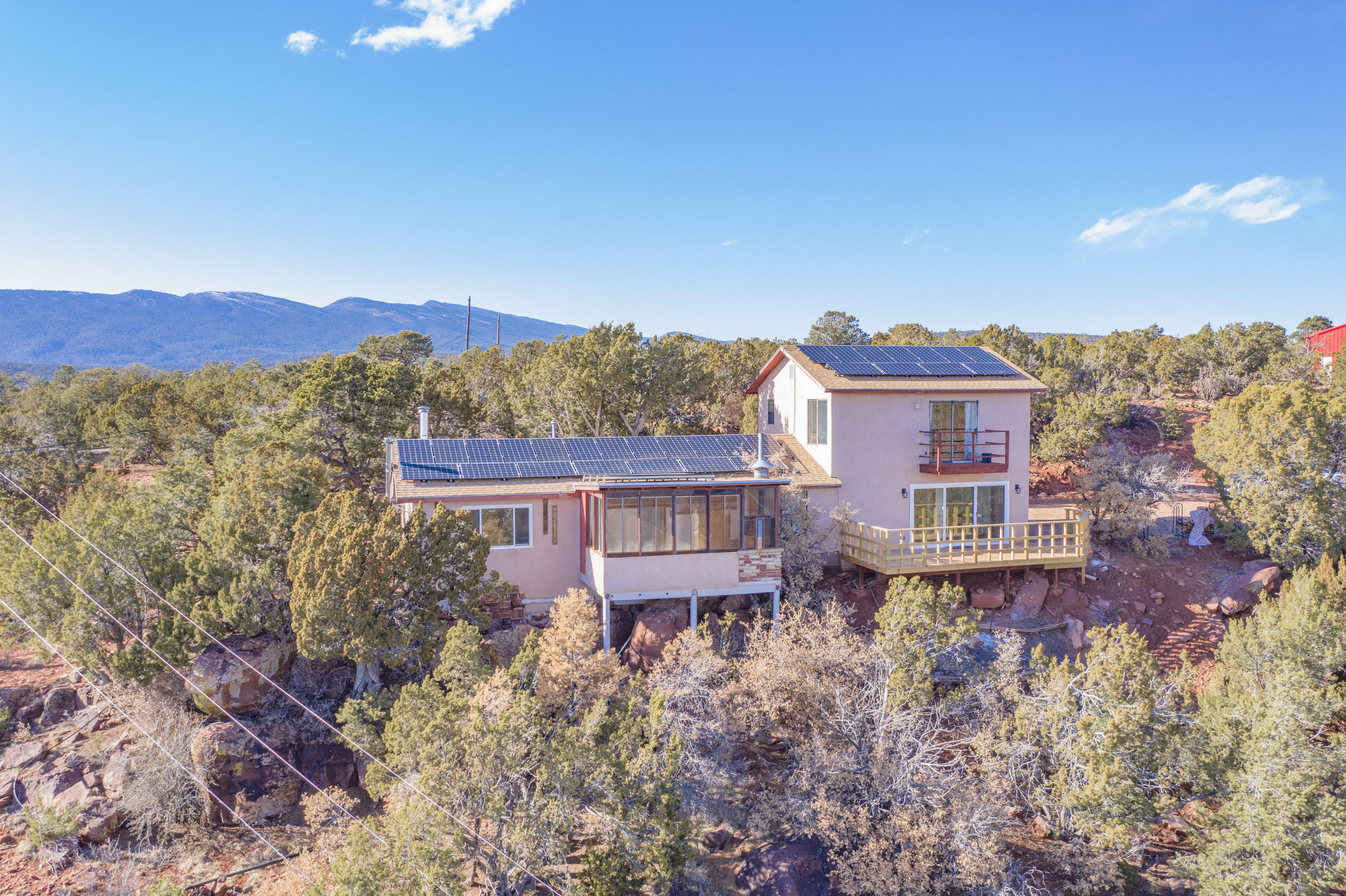 Views, Views Views! and privacy too!2 five acre lots, private well, dead end privacy. Brand new deck, 35 solar panels that supplement the electric and feed back to PNM. Wood stove for those cold winter nights. Updated, remodeled bathrooms, new carpet., new water heater. New 30x40 metal shop w/ 15 FT ceiling